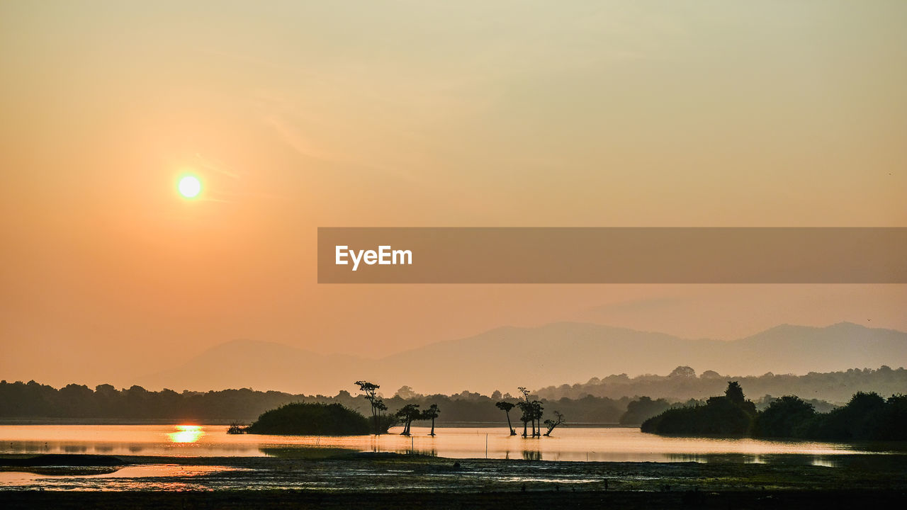 SCENIC VIEW OF LAKE BY SILHOUETTE MOUNTAINS AGAINST ORANGE SKY
