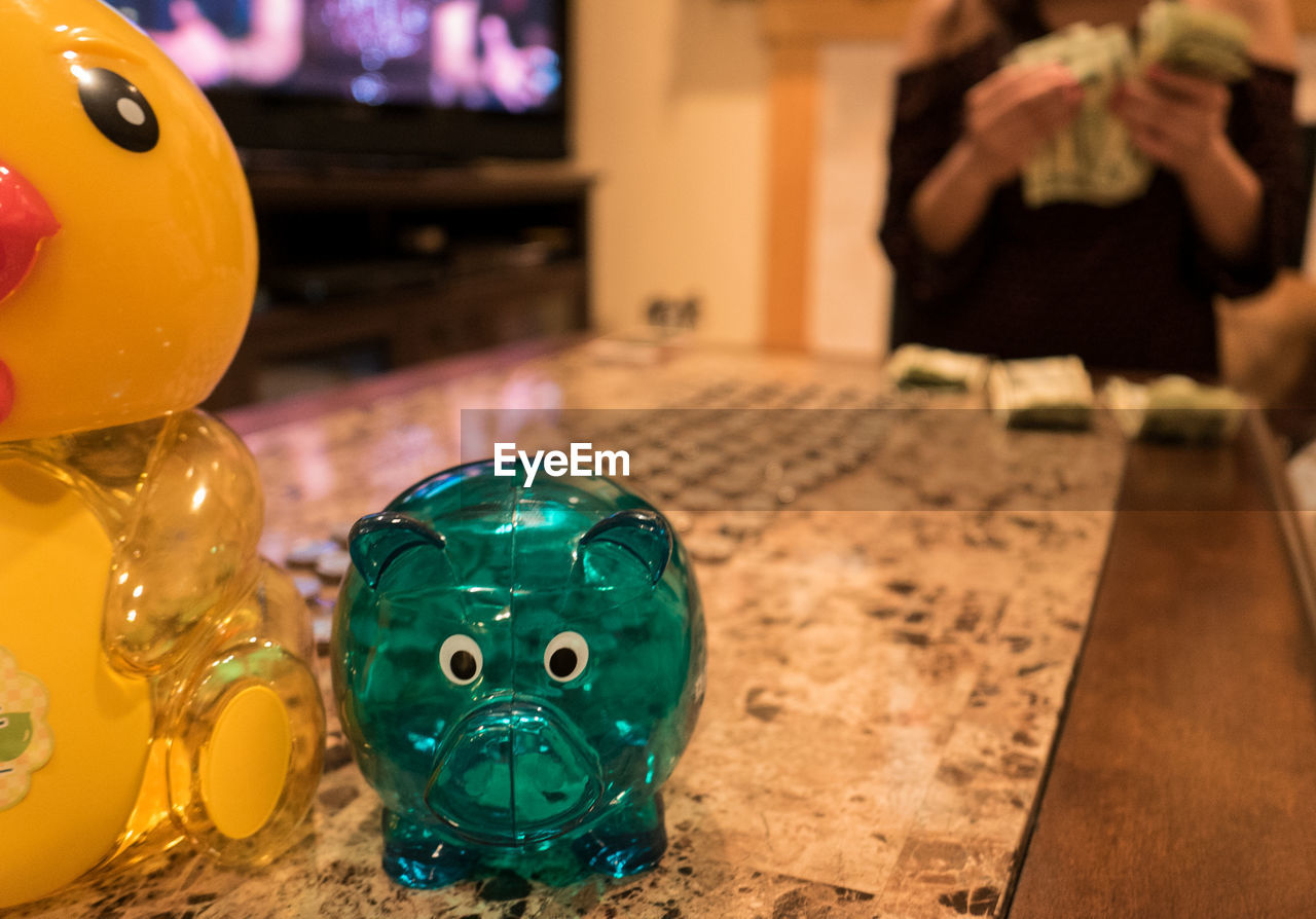 Piggy Bank On Table With Person Counting Currency In Background At Home