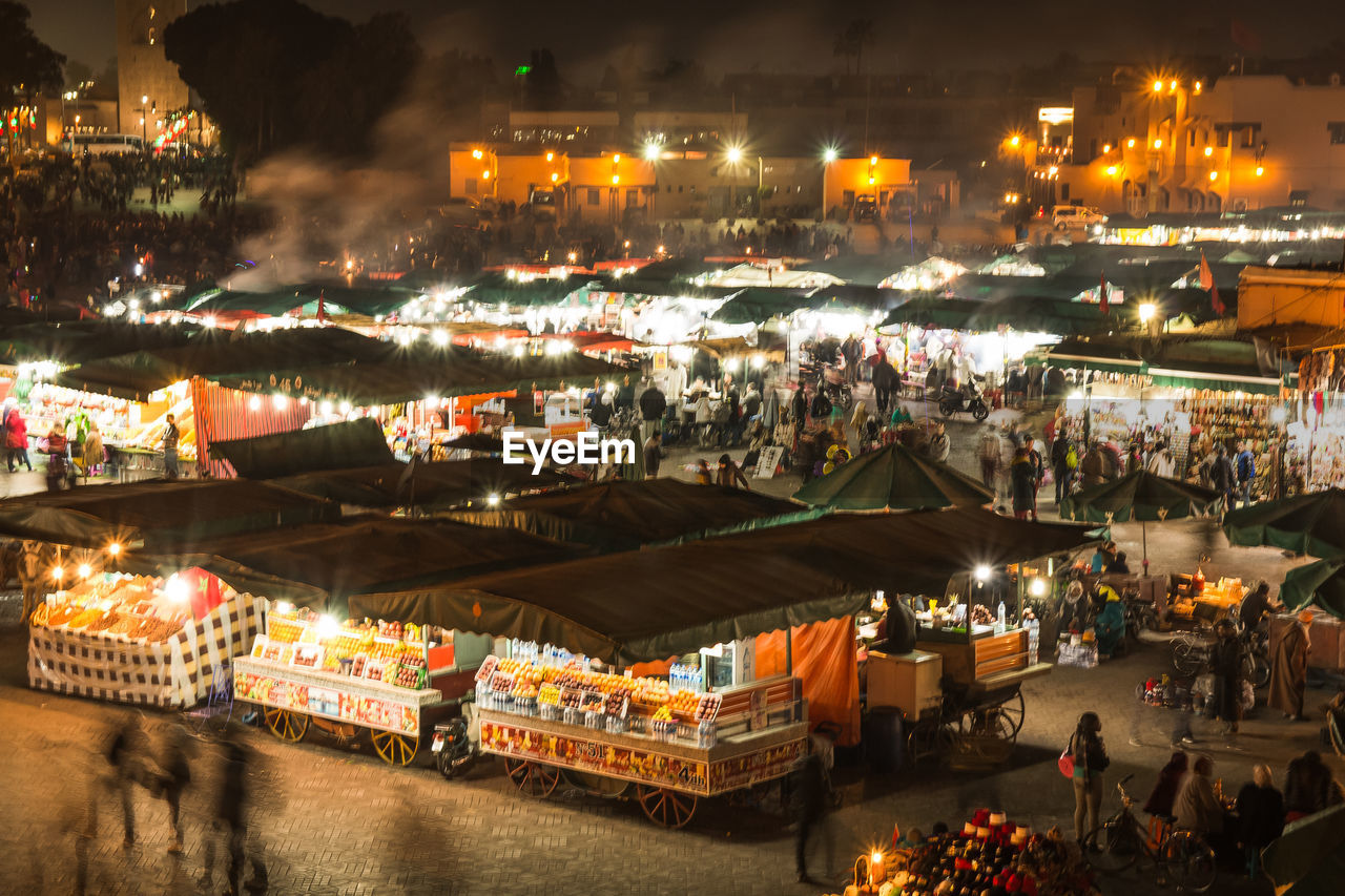 illuminated, night, architecture, water, city, built structure, transportation, building exterior, real people, market, nautical vessel, business, mode of transportation, high angle view, incidental people, blurred motion, crowd, travel, nature, outdoors, consumerism