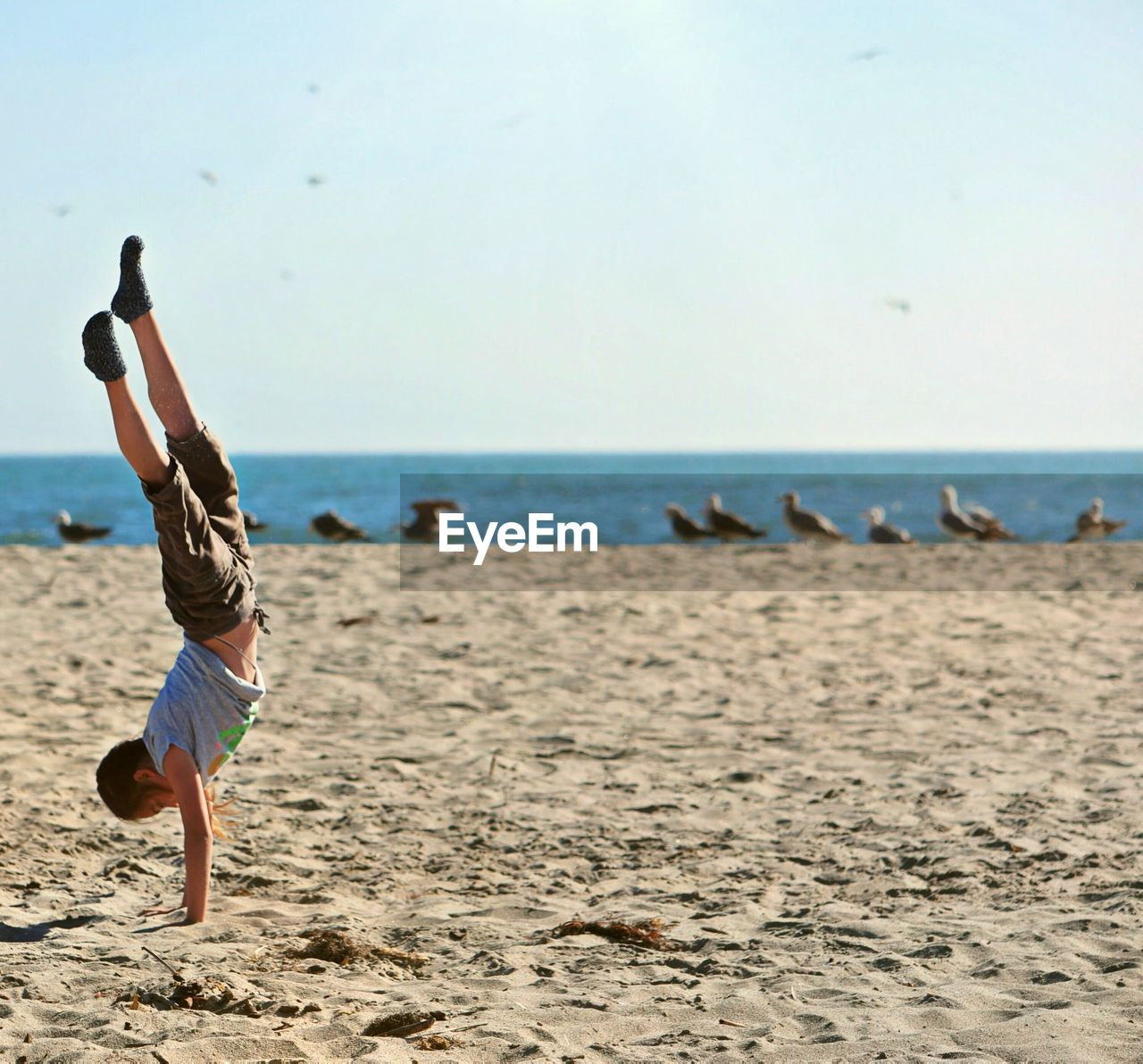 Side View Of Boy Doing Handstand At Beach Against Sky