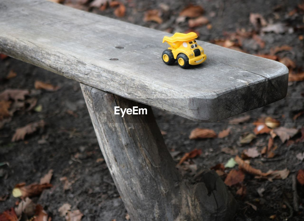 Close-up of yellow toy car on bench
