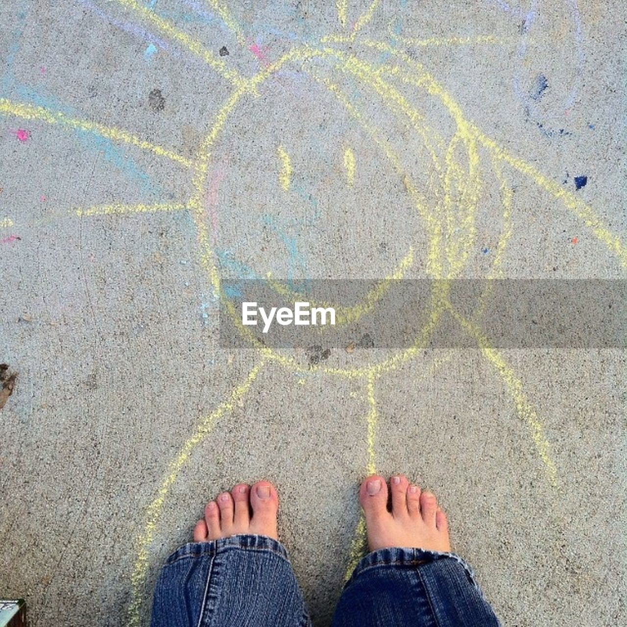 Low section of child standing on ground with smiley chalk sun face on concrete