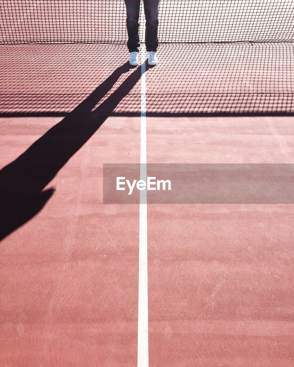 Low section of man standing on tennis court