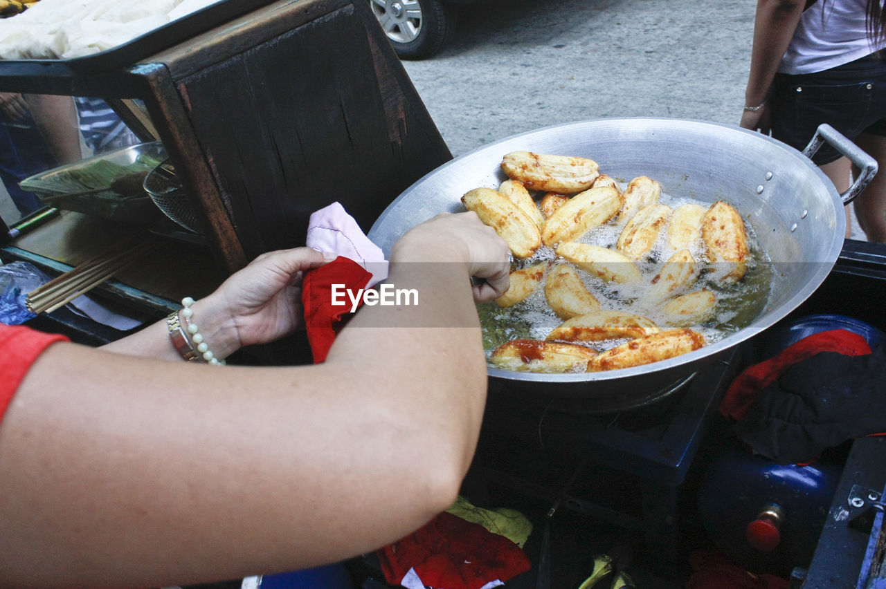 Cropped image of woman frying food at street
