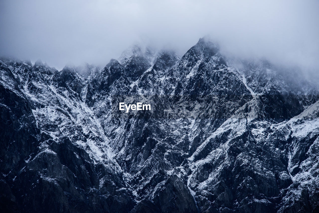 Close-Up Of Snow On Mountain Against Sky