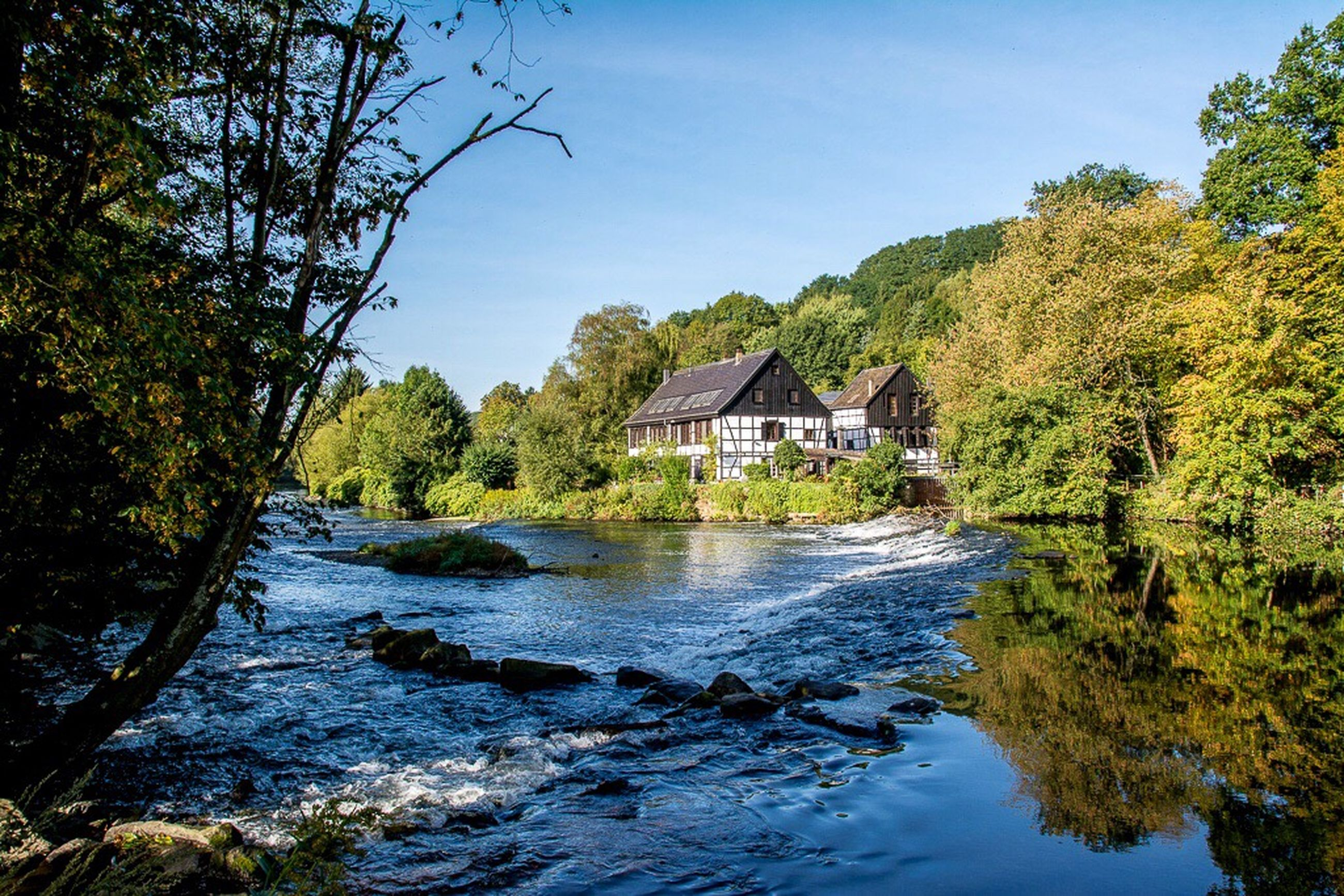 water, tree, house, architecture, built structure, river, scenics, tranquil scene, building exterior, tranquility, stream, flowing, flowing water, non-urban scene, mountain, nature, remote, beauty in nature, blue, day, riverbank, outdoors, tourism, narrow, sky, waterfront, green color