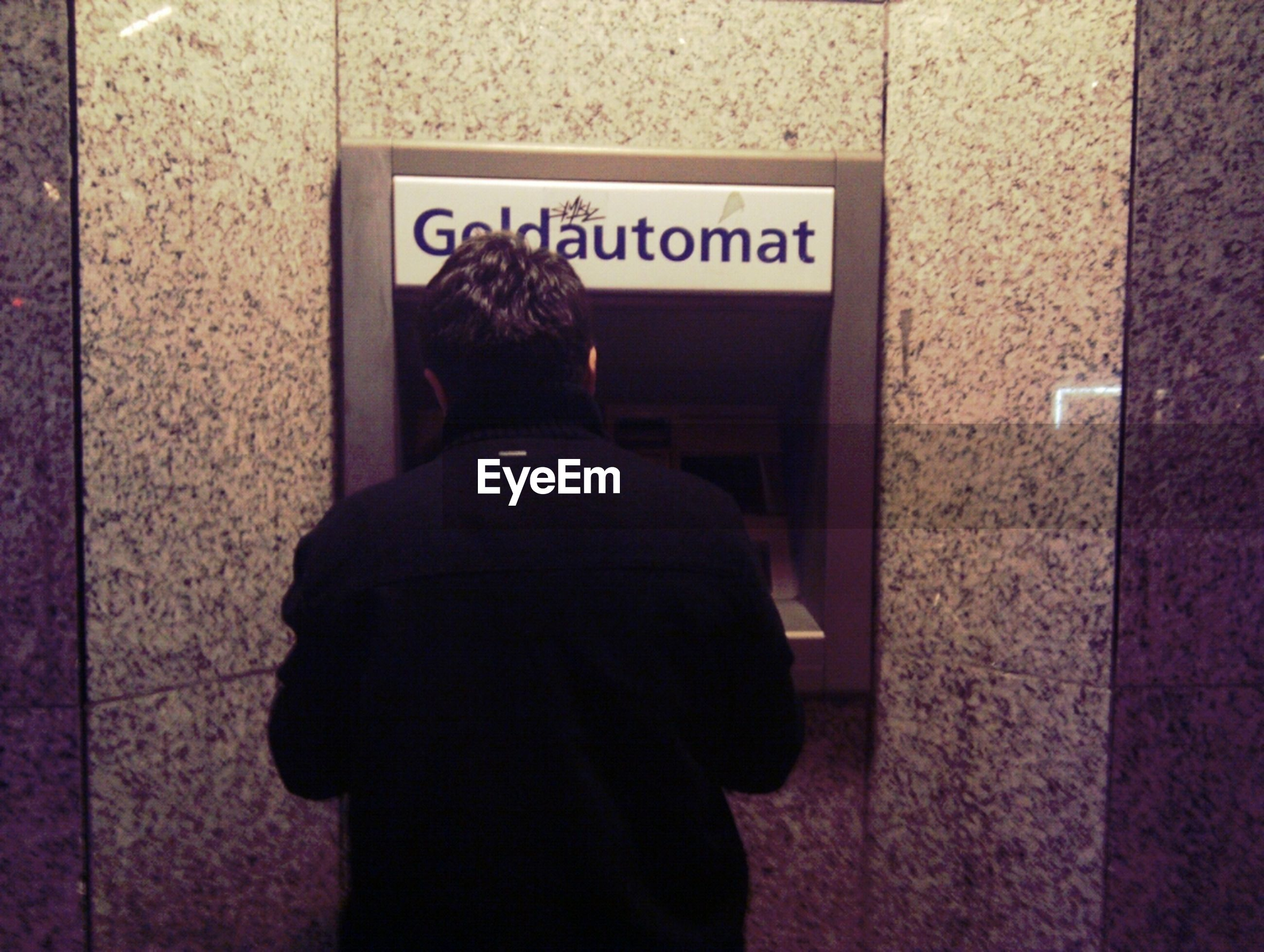 Rear view of person withdrawing money at cash machine
