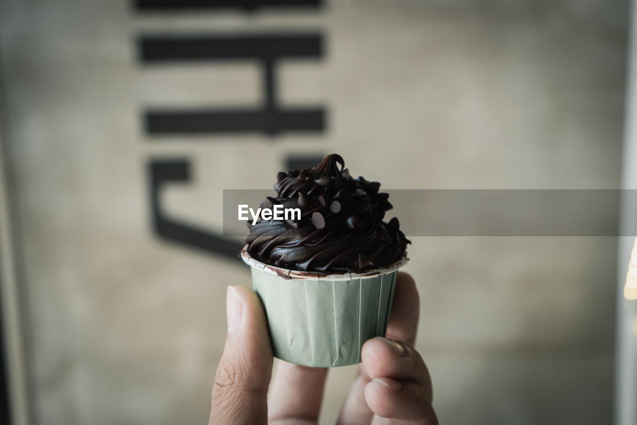 Close-Up Of Hand Holding Chocolate Cupcake
