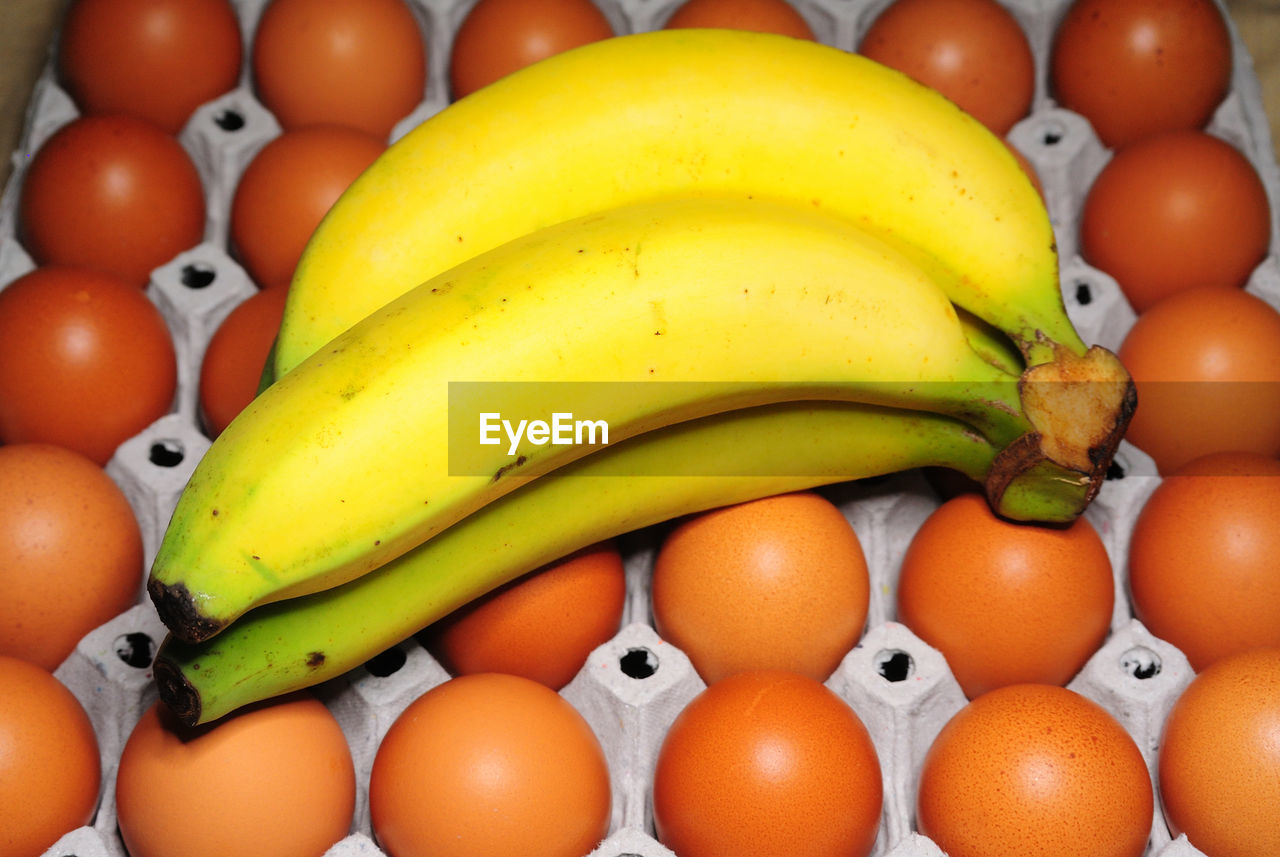 High angle view of bananas on brown eggs in carton