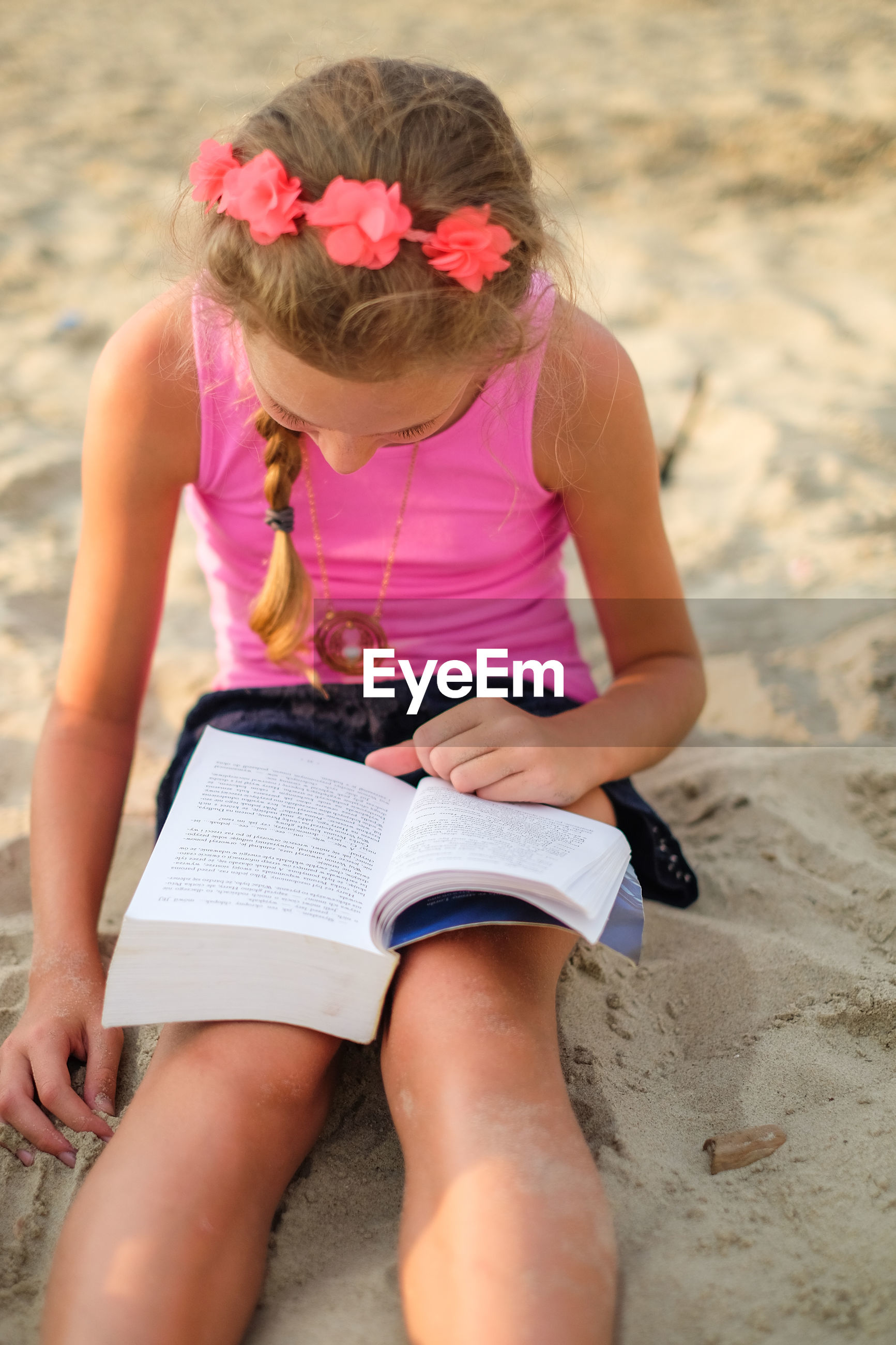 Girl reading book while sitting on beach