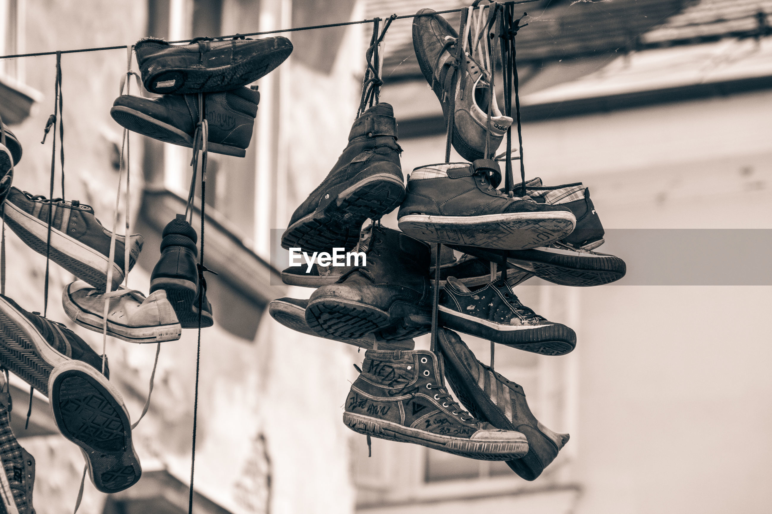 LOW ANGLE VIEW OF SHOES HANGING ON METAL AGAINST THE SKY