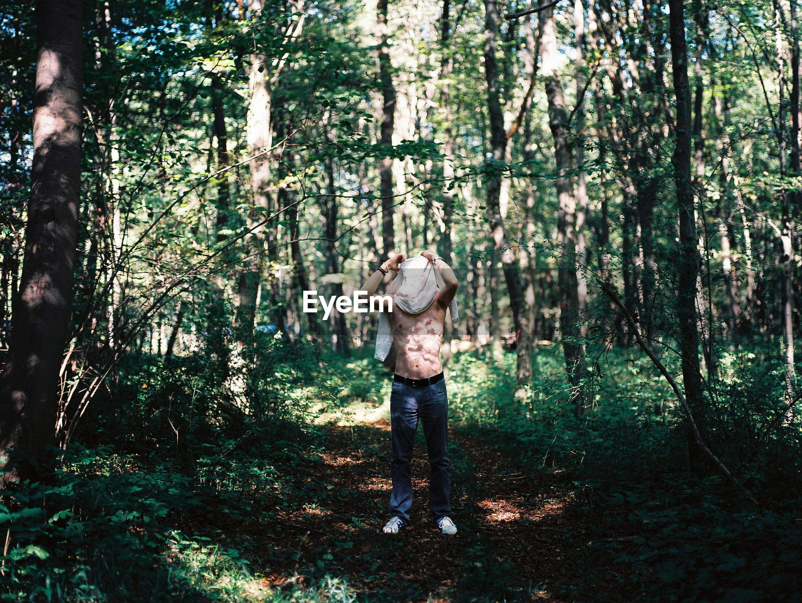 Full length of shirtless man standing in forest