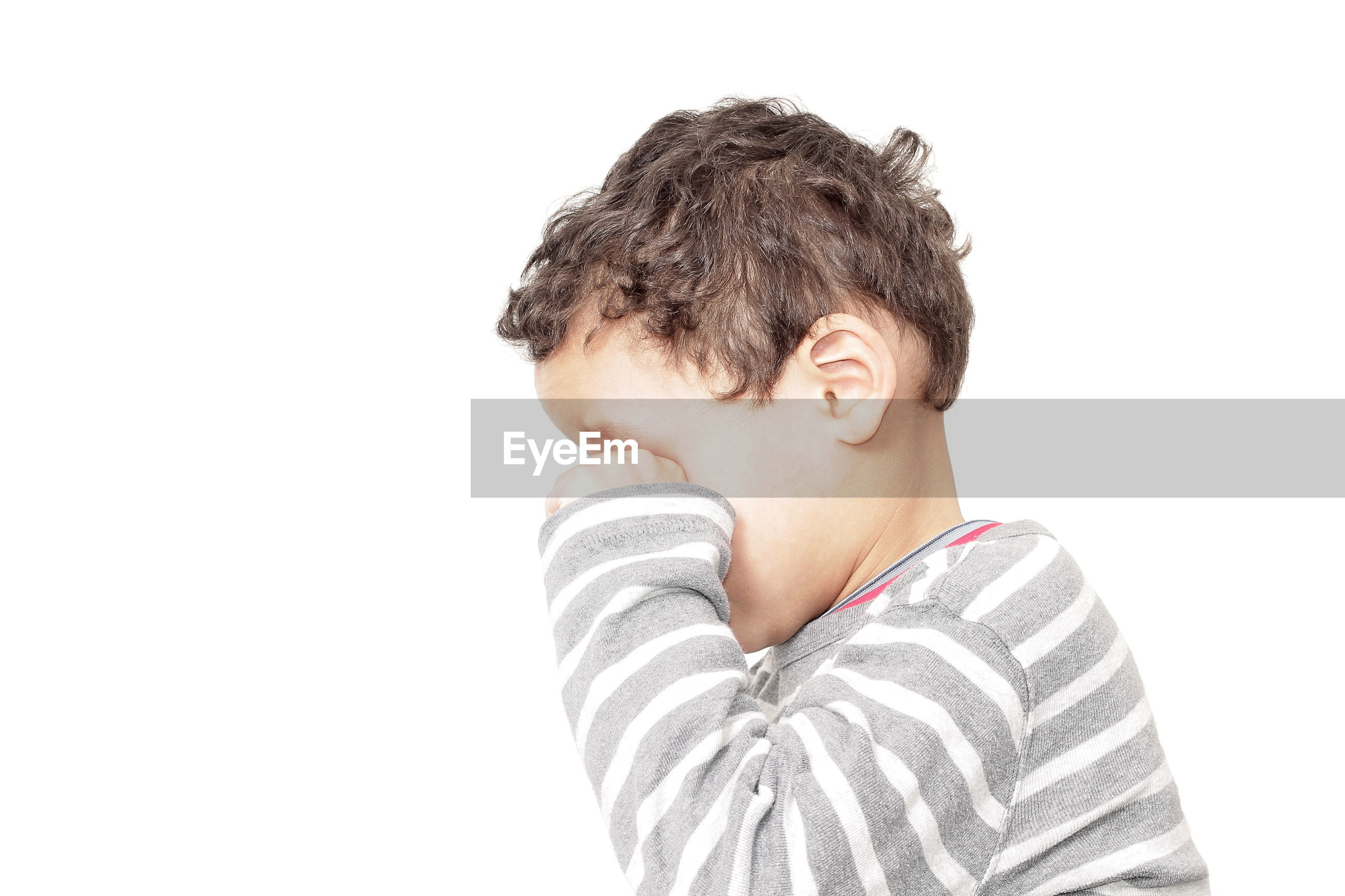 Close-up of boy crying against white background