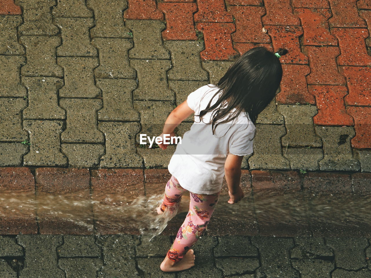 Rear view of girl standing on wet street during rainy season