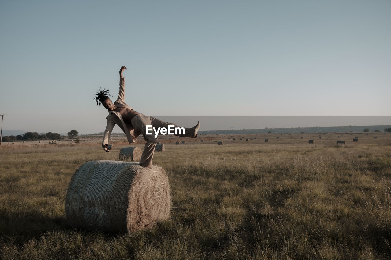 Young man standing on hay bale at agricultural landscape