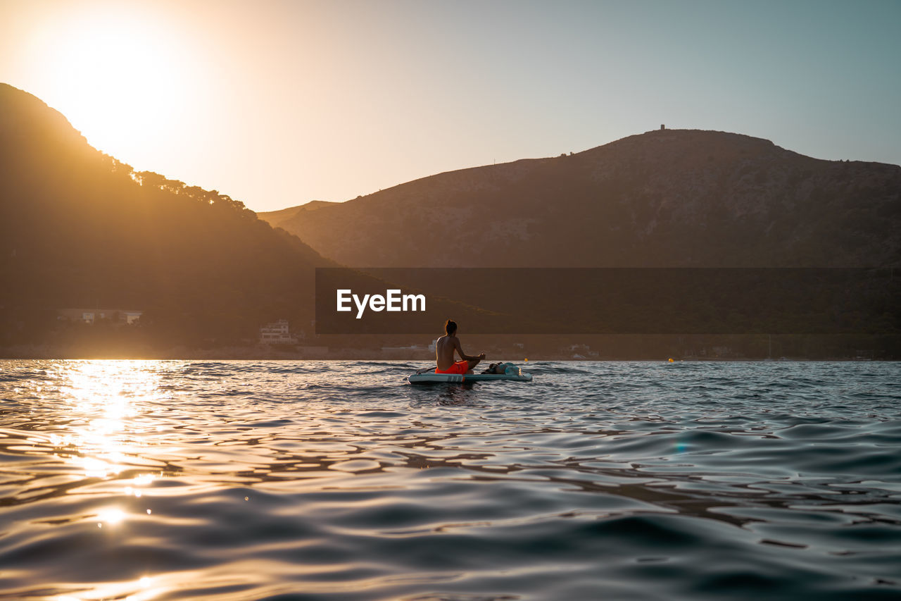 Man sitting on boat in lake against sky during sunset