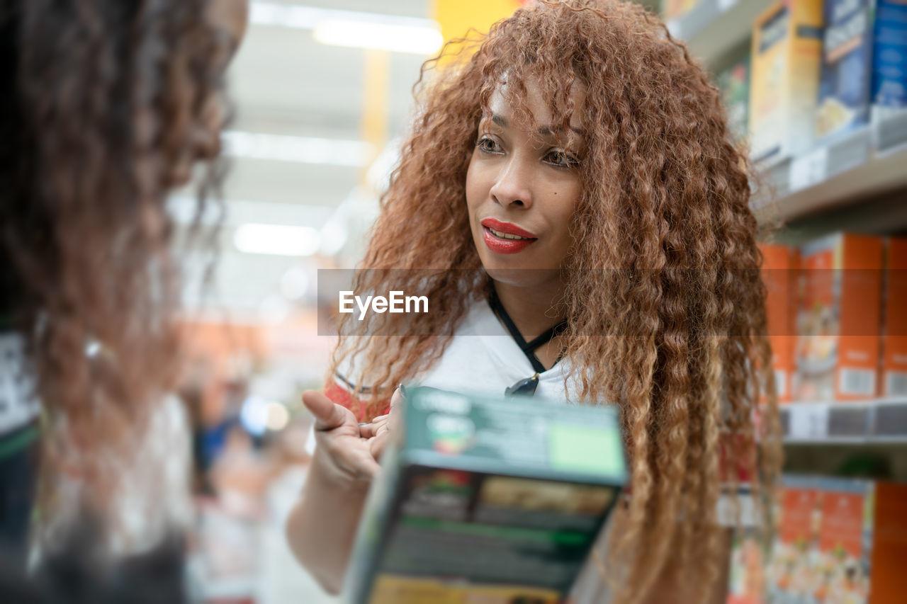 Woman pointing at box while talking friend at supermarket