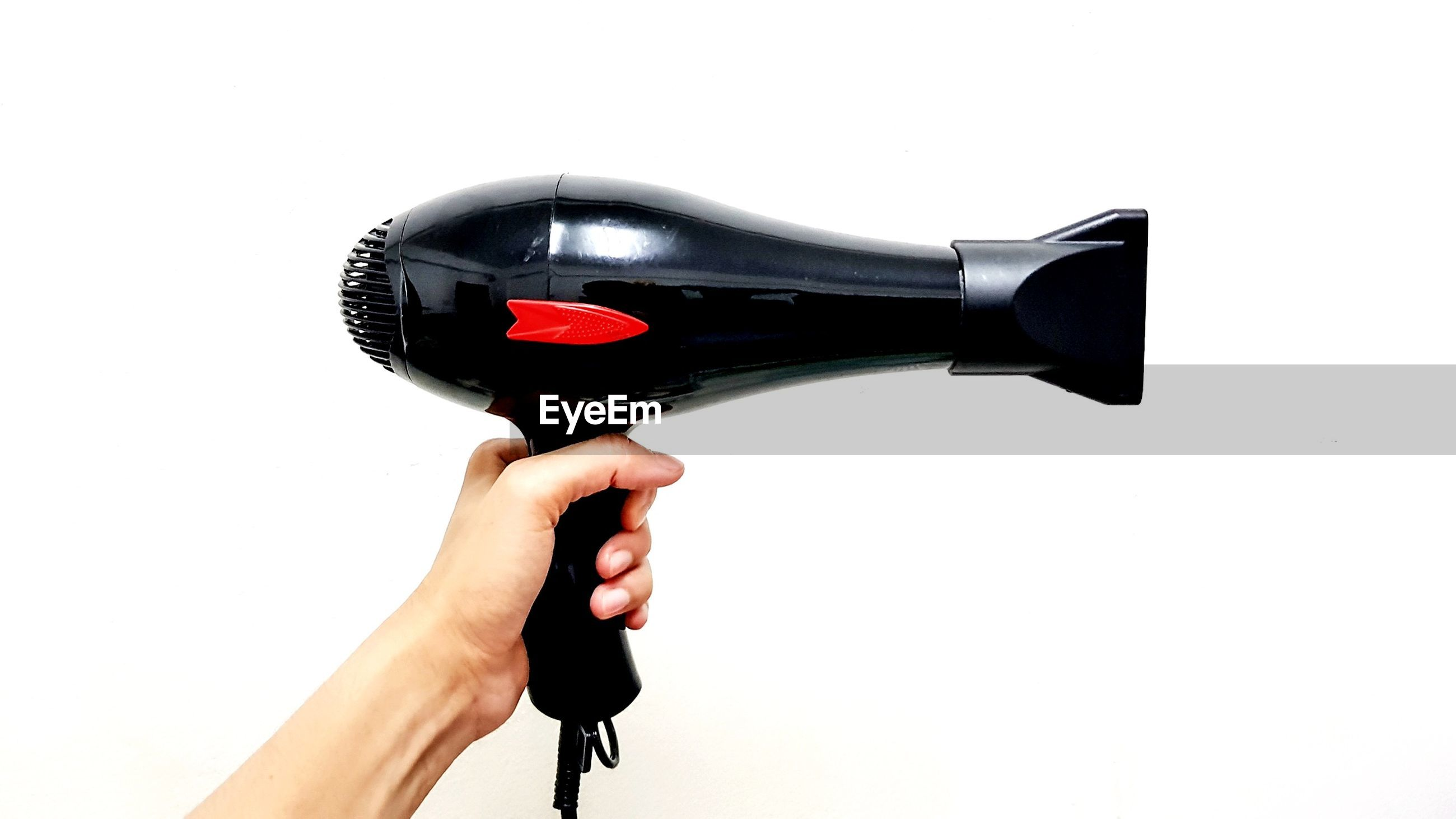 Cropped hand holding hair dryer against white background