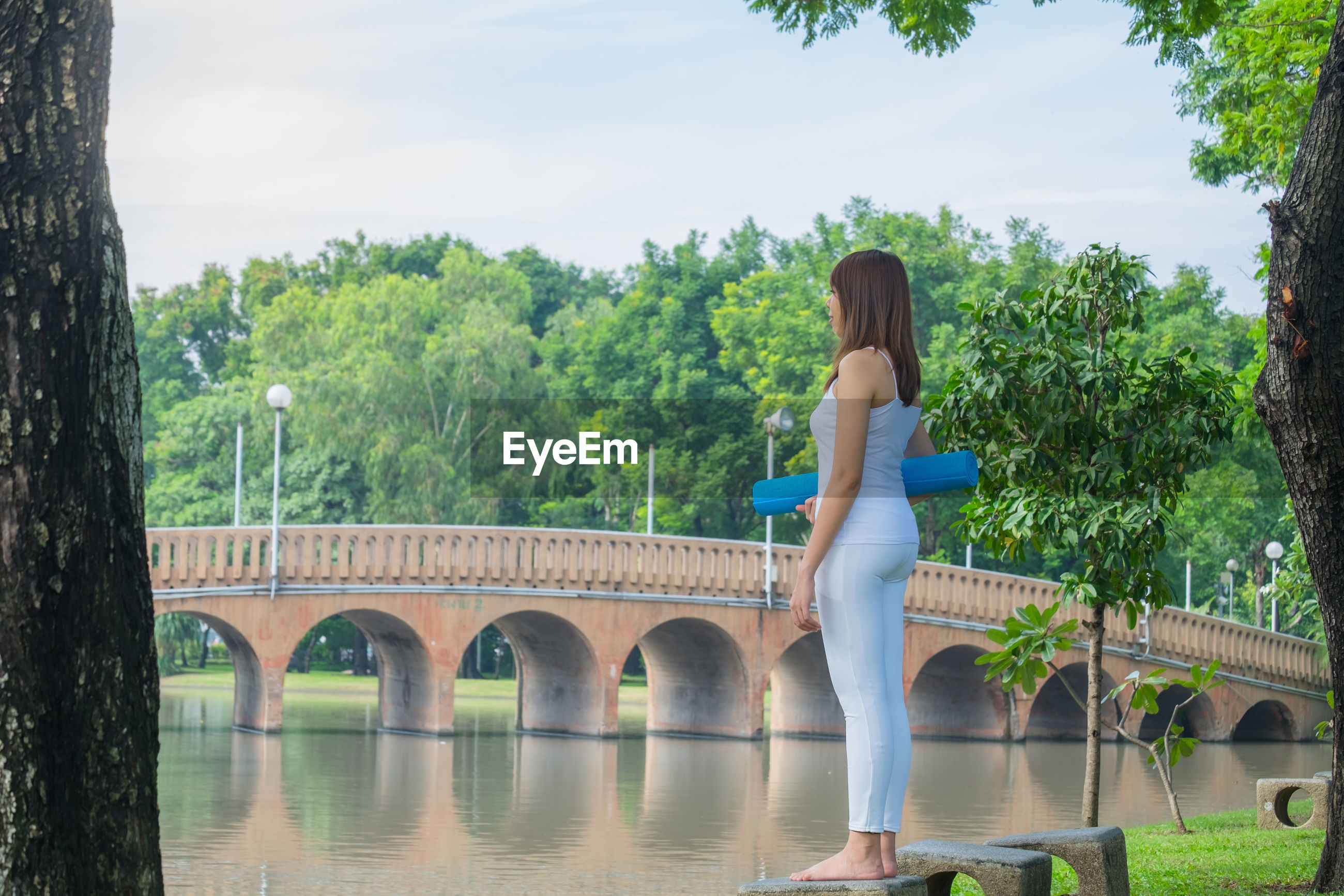 Woman by river against trees and sky