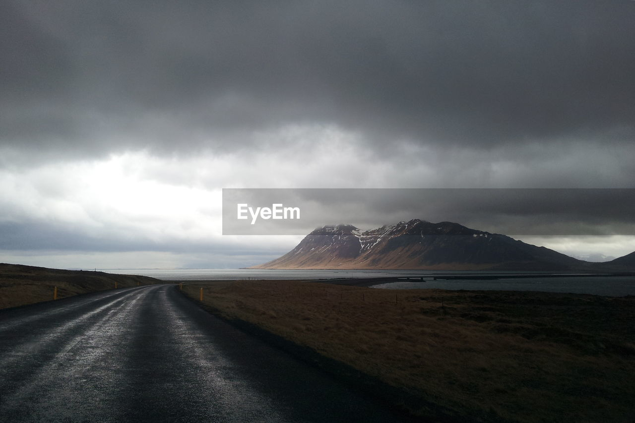 Scenic view of road by beach against storm clouds