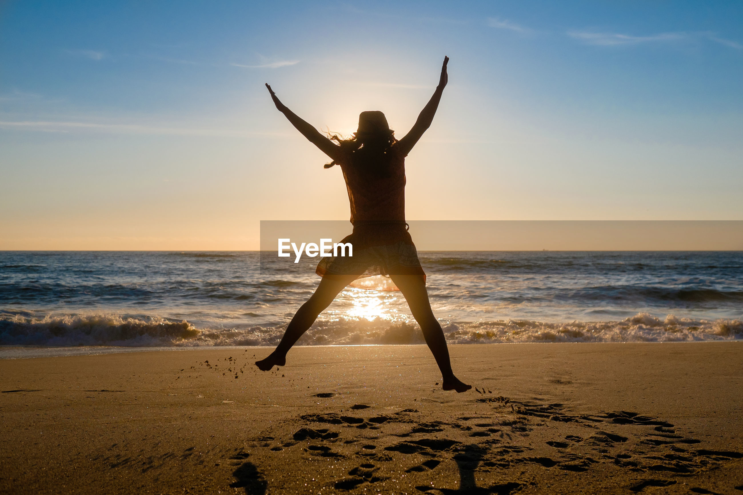Rear view of woman jumping on beach