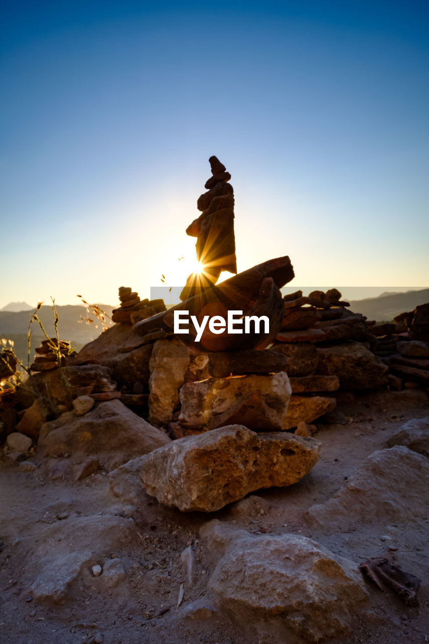 sky, rock, solid, rock - object, sunset, nature, tranquility, rock formation, sunlight, no people, beauty in nature, scenics - nature, non-urban scene, tranquil scene, lens flare, sun, clear sky, stack, balance, orange color, outdoors, eroded