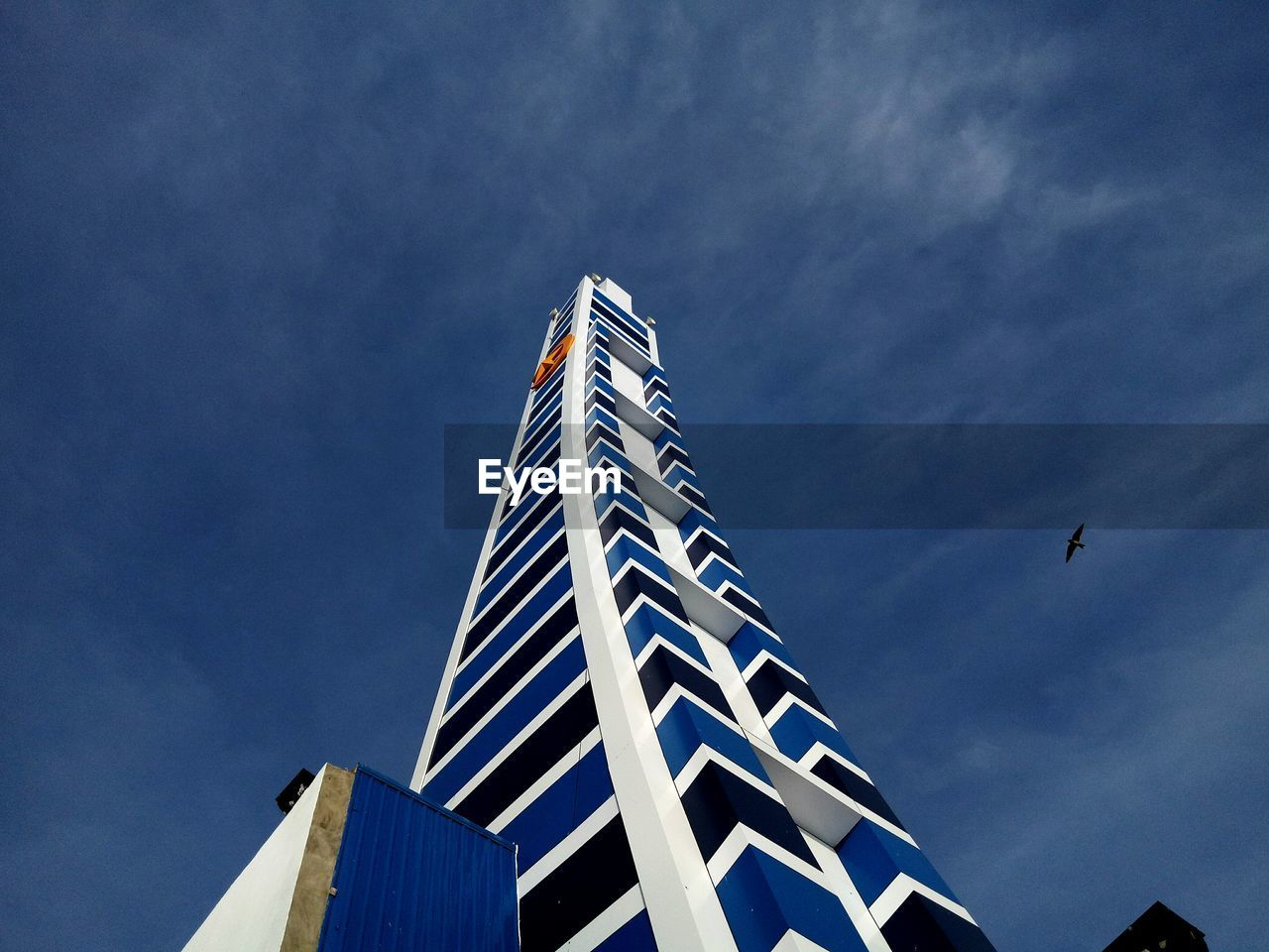 sky, low angle view, architecture, built structure, building exterior, nature, building, no people, cloud - sky, day, blue, city, modern, outdoors, office building exterior, animal themes, vertebrate, bird, animal, animals in the wild, skyscraper, apartment