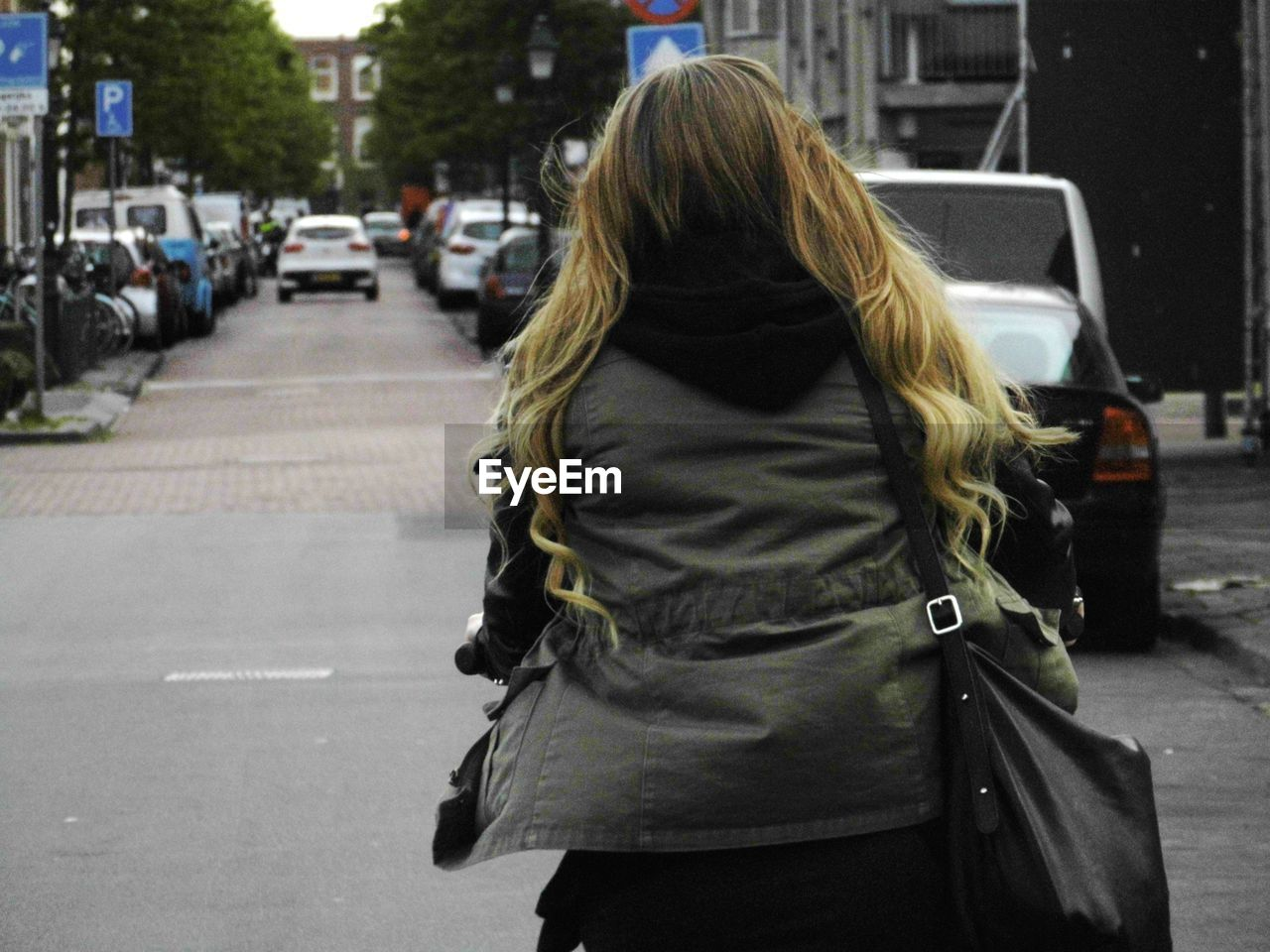 Rear view of woman with jacket on city street