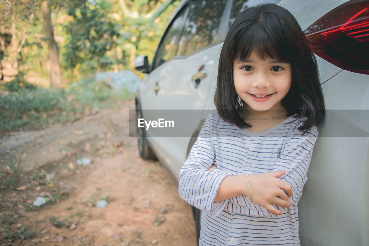 Portrait of smiling girl standing by car