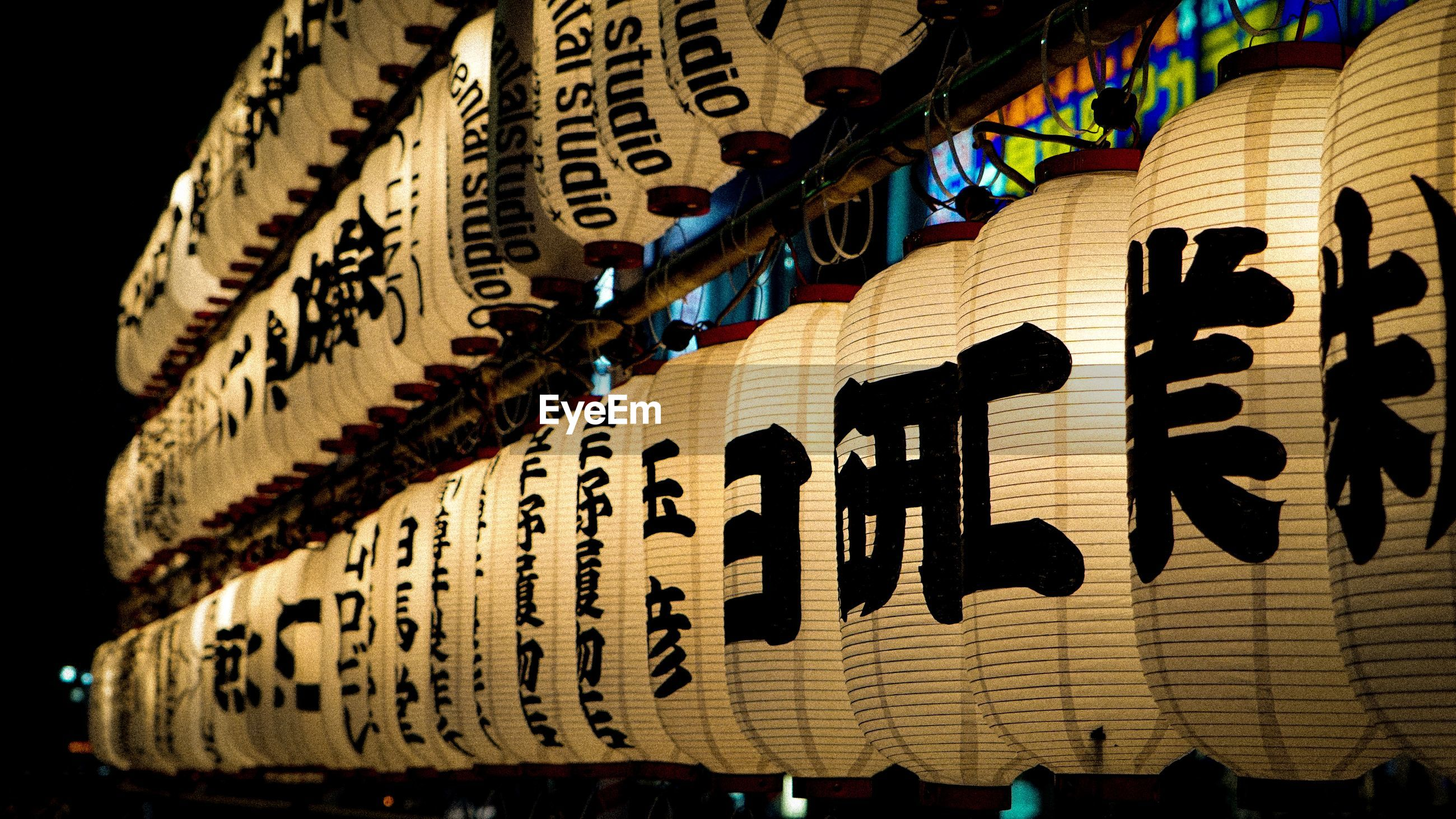 text, communication, no people, script, non-western script, western script, hanging, close-up, focus on foreground, lantern, decoration, indoors, sign, pattern, textile, information, night, religion, belief, paper lantern