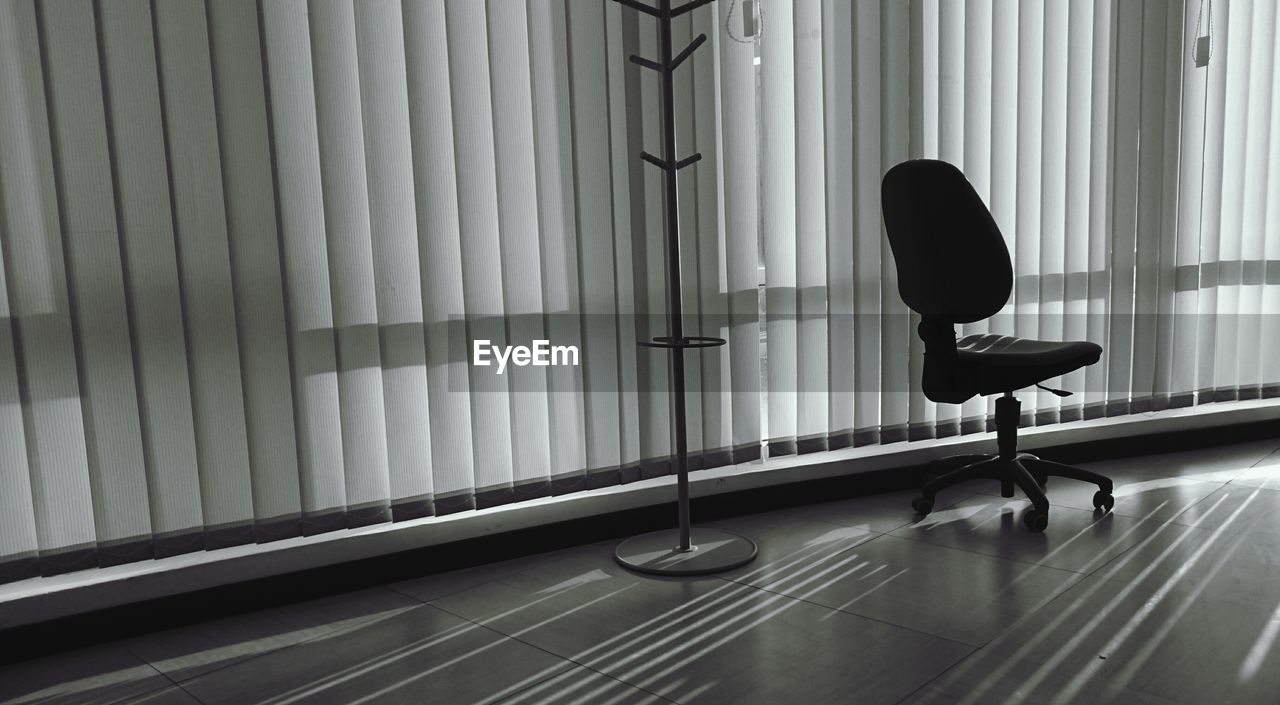 Empty chair by window blinds in office