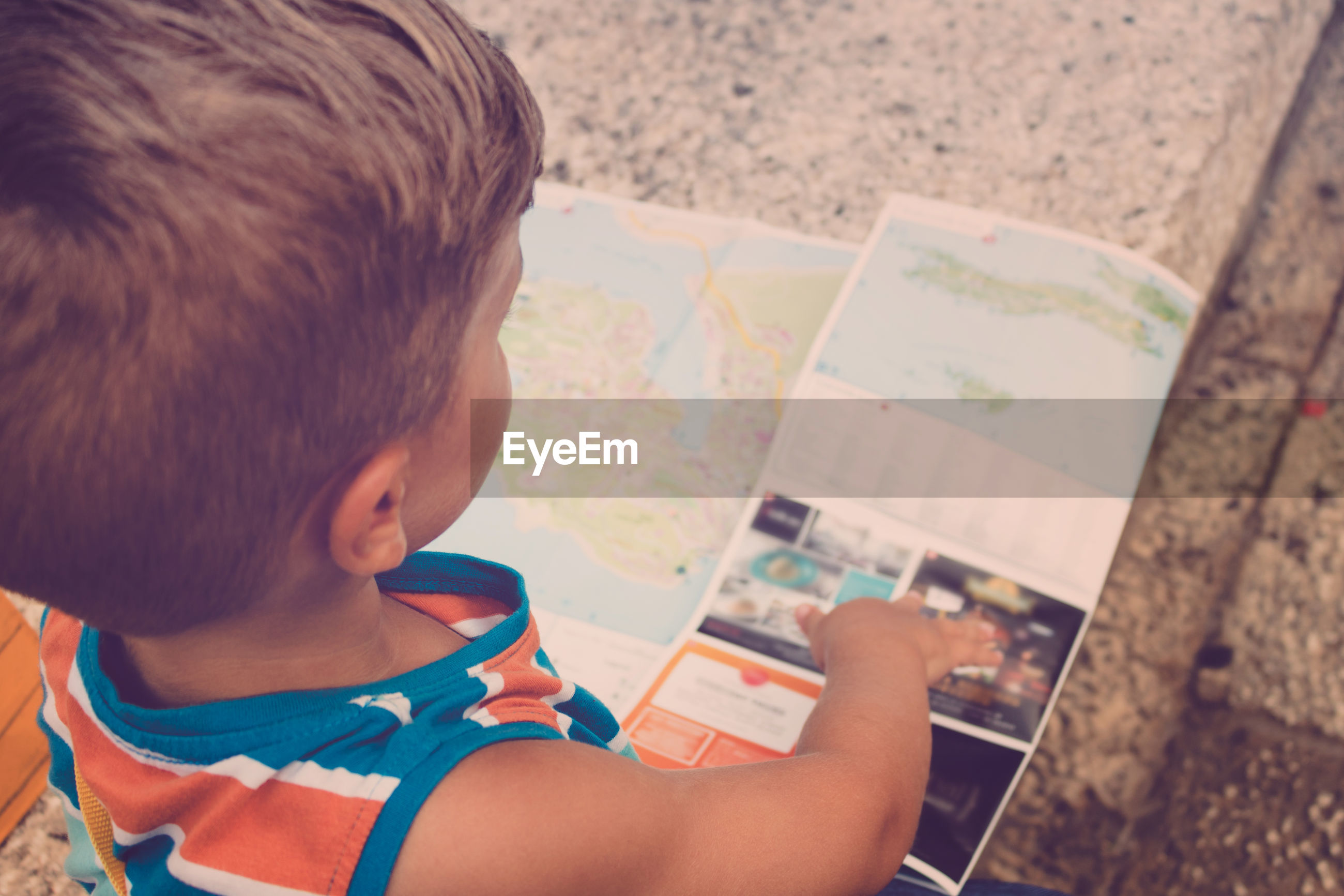 High angle view of boy looking at world map