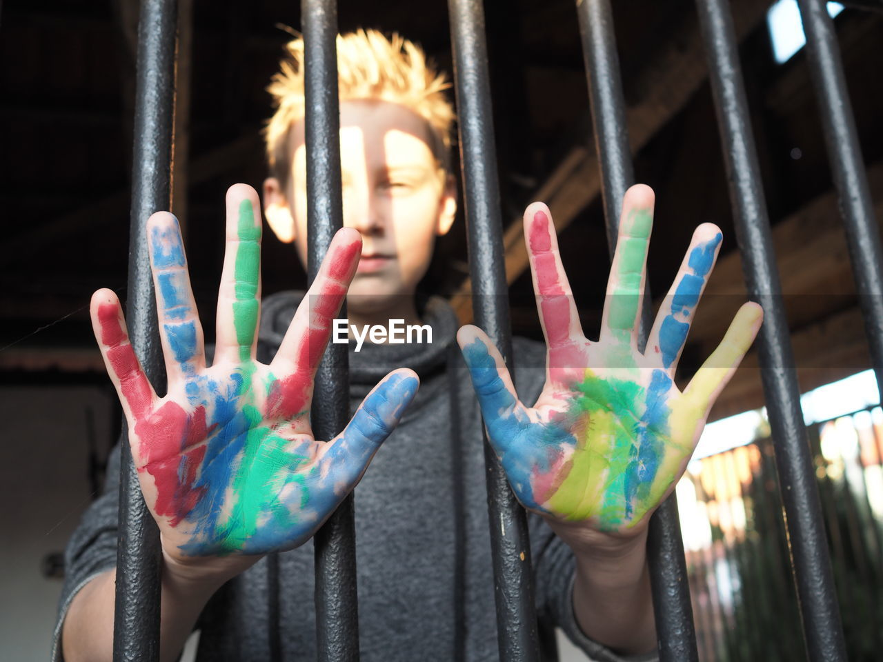 Portrait Of Teenage Boy Showing Painted Hands Behind Fence