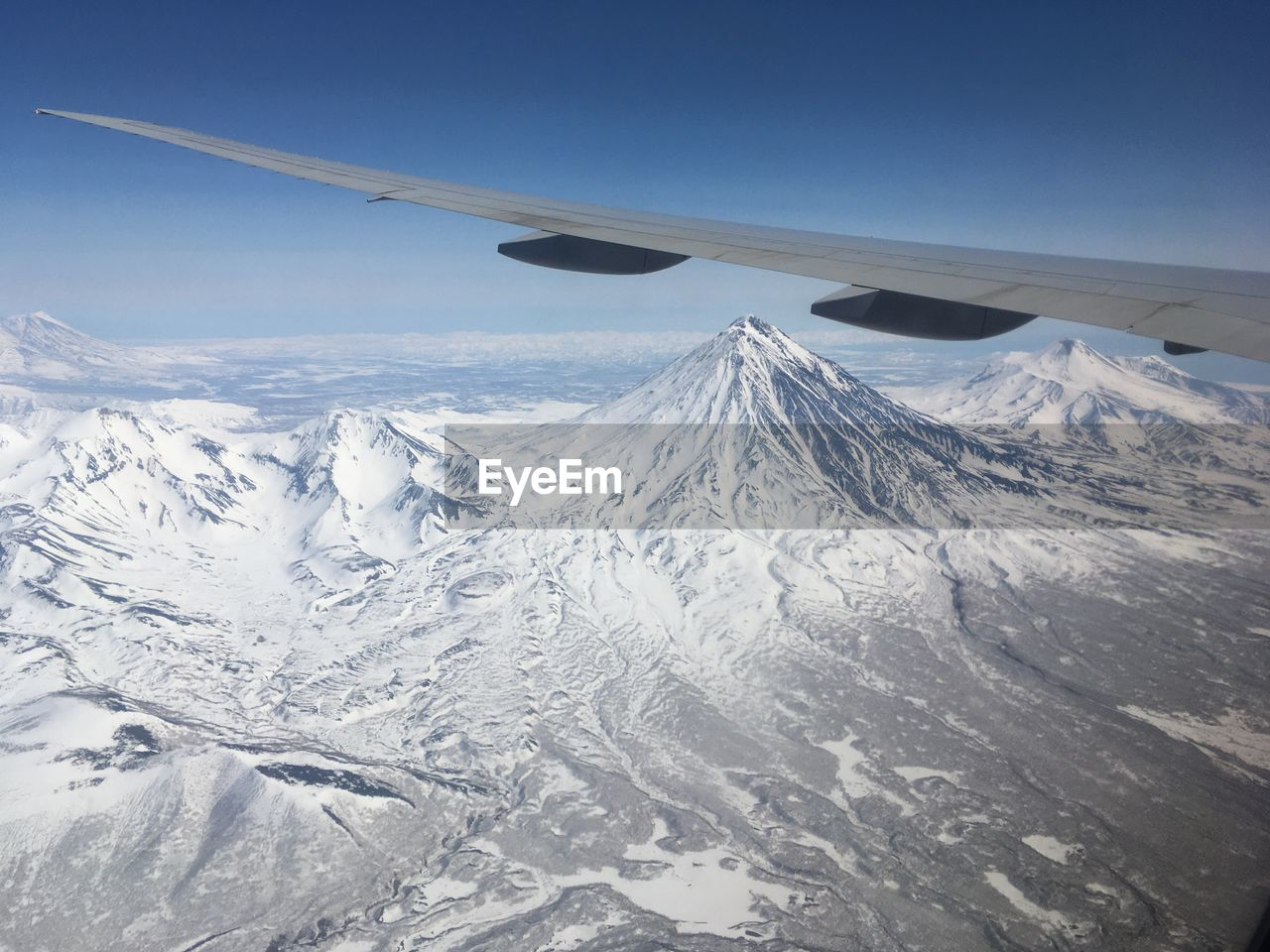 Aircraft over snowcapped mountains against sky