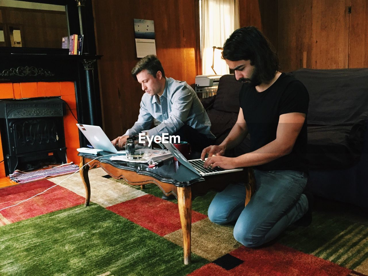 Two Serious Young Men Using Laptops