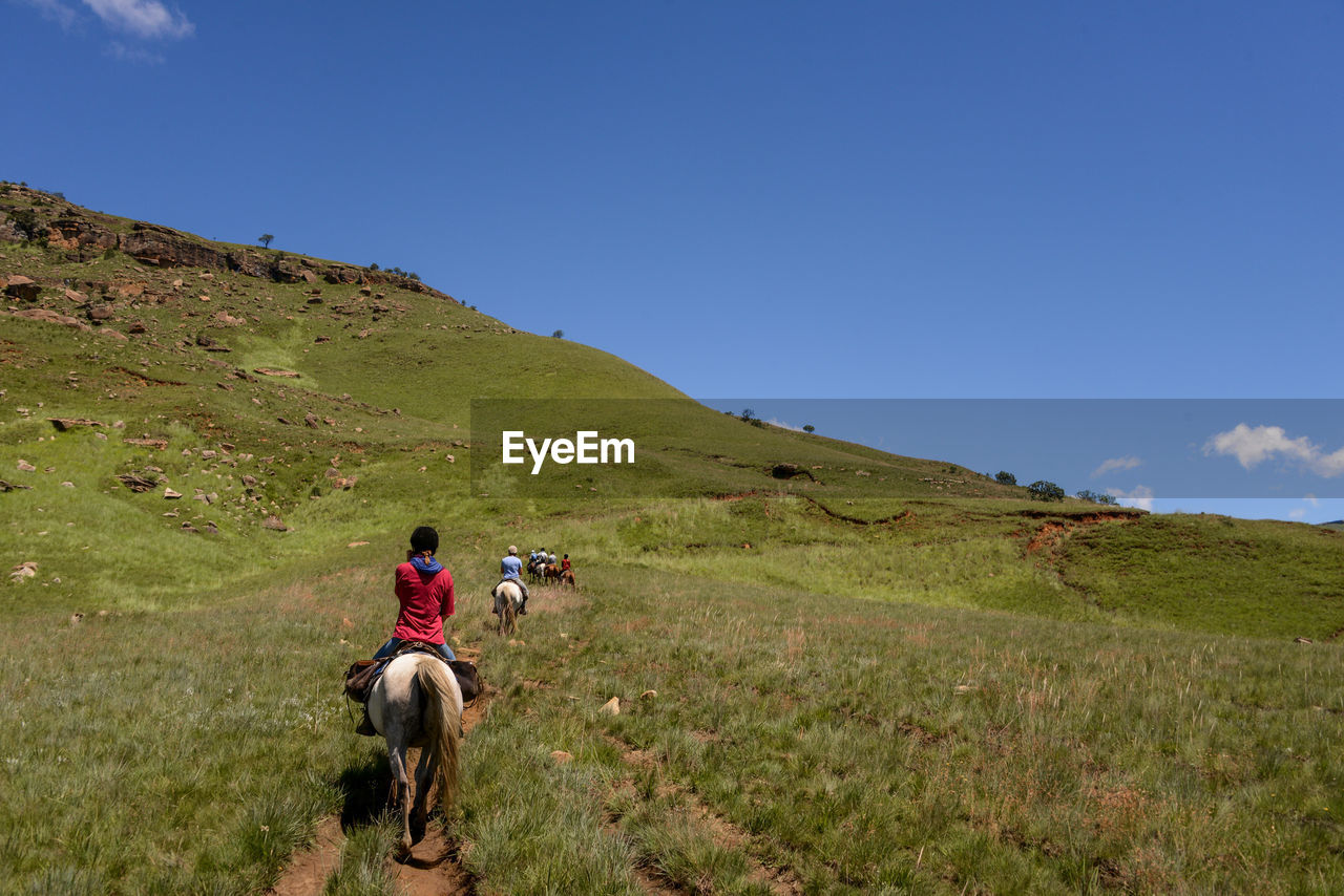 REAR VIEW OF PEOPLE RIDING HORSE ON FIELD AGAINST MOUNTAIN