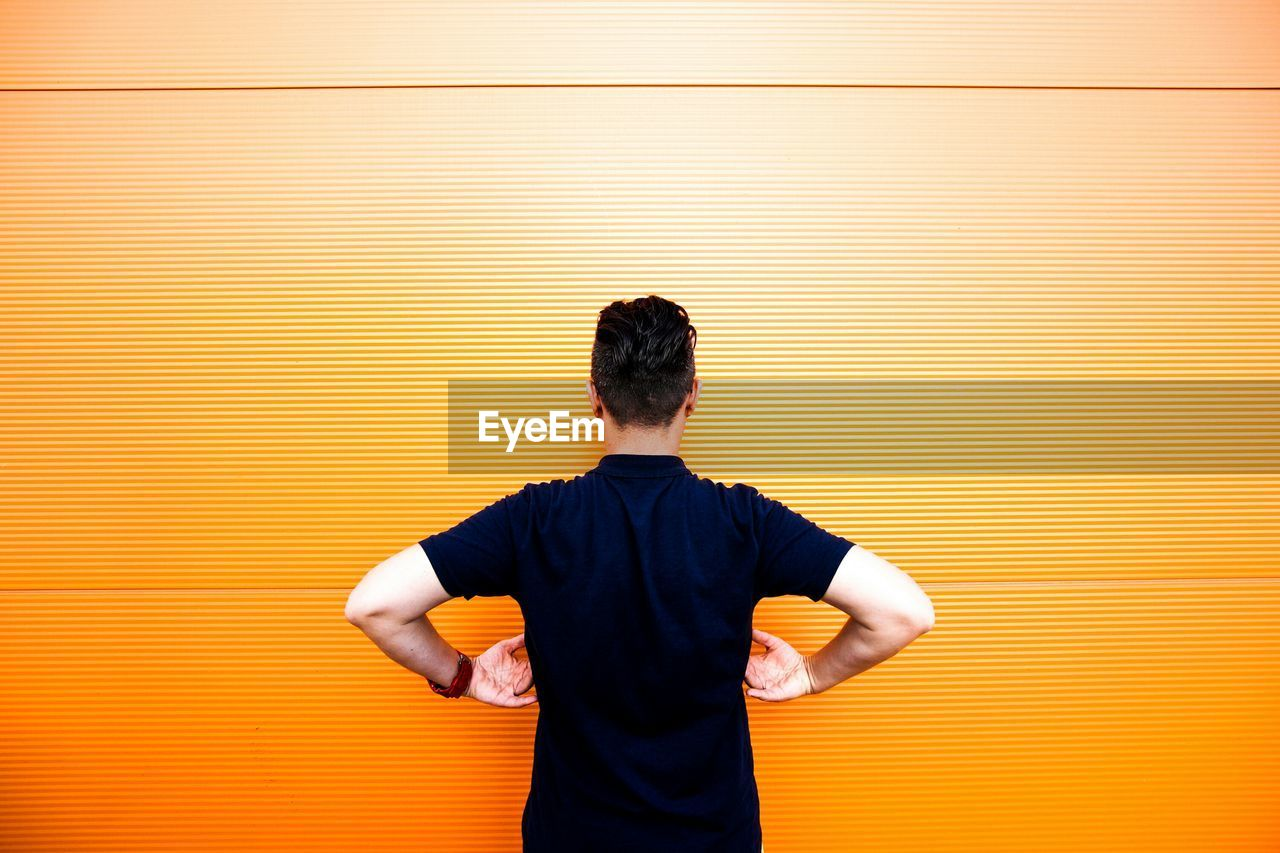 Rear View Of Man Standing Against Orange Wall
