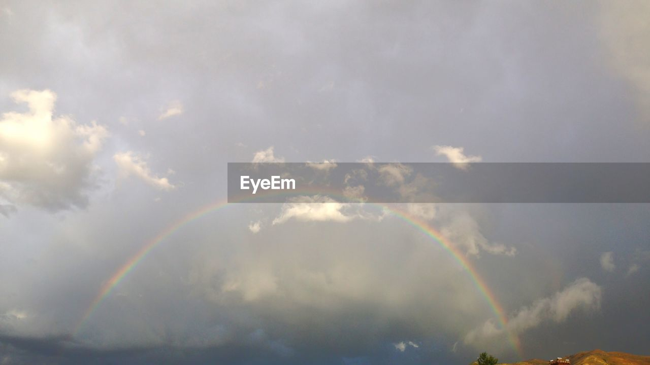 cloud - sky, rainbow, beauty in nature, sky, scenics - nature, low angle view, no people, nature, tranquility, day, idyllic, tranquil scene, outdoors, double rainbow, sunlight, natural phenomenon, multi colored, non-urban scene, lens flare, meteorology