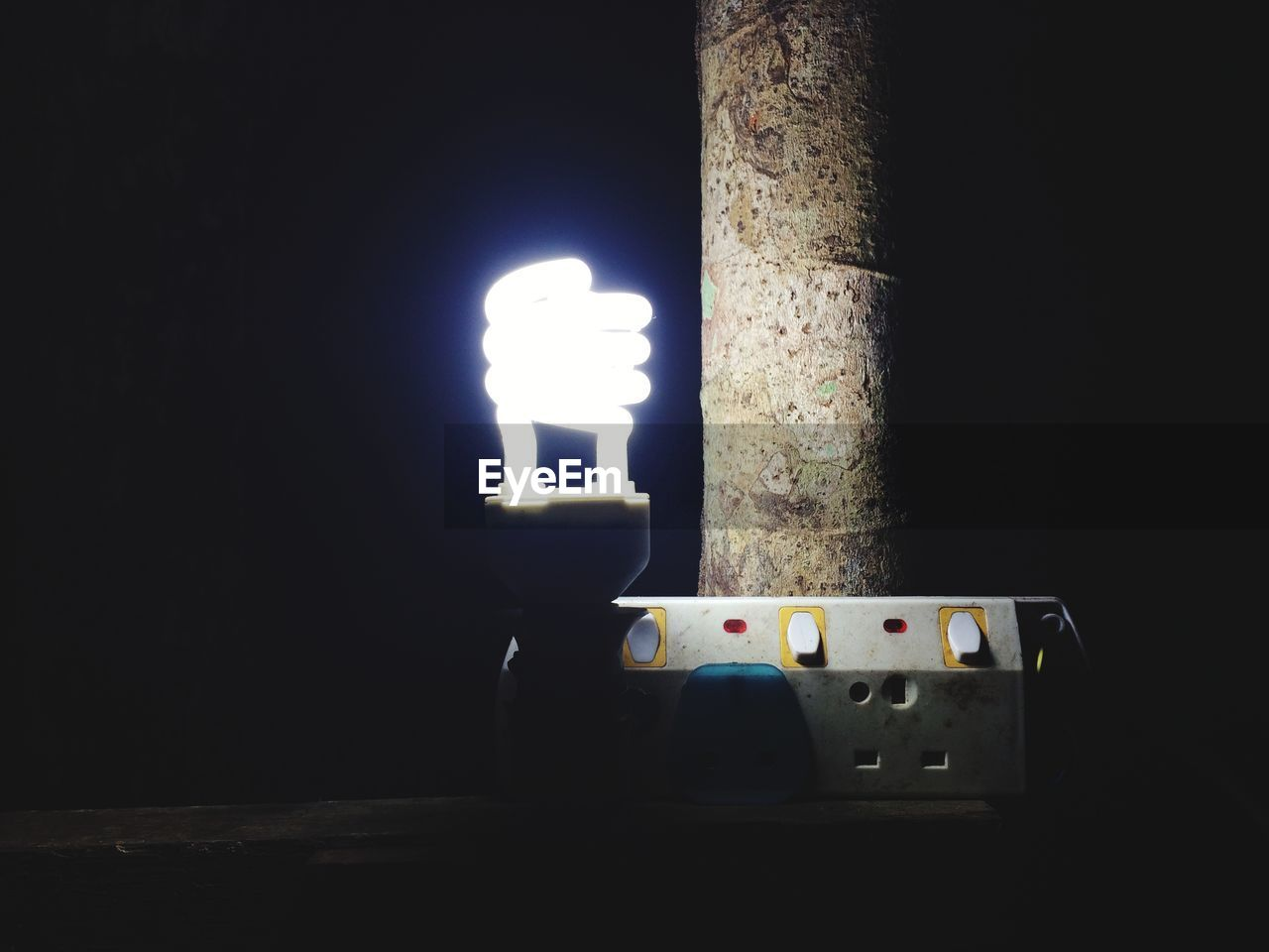 illuminated, no people, electricity, night, glowing, technology, lighting equipment, close-up, indoors, dark, light bulb, light - natural phenomenon, copy space, still life, fuel and power generation, domestic room, wall - building feature, nature, energy efficient, light, black background, power supply, push button, electrical equipment, brightly lit