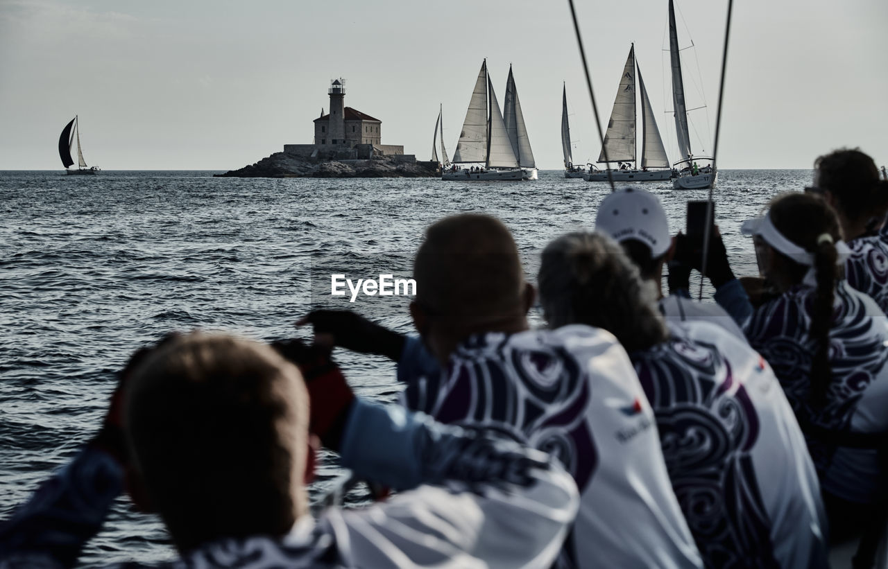 REAR VIEW OF PEOPLE ON SAILBOAT