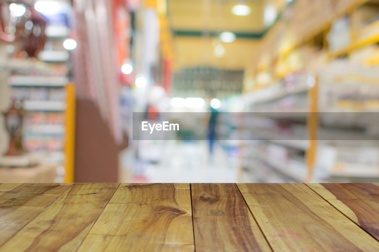 focus on foreground, indoors, wood - material, table, no people, close-up, illuminated, still life, flooring, empty, in a row, architecture, business, wood, selective focus, for sale, seat, choice, absence