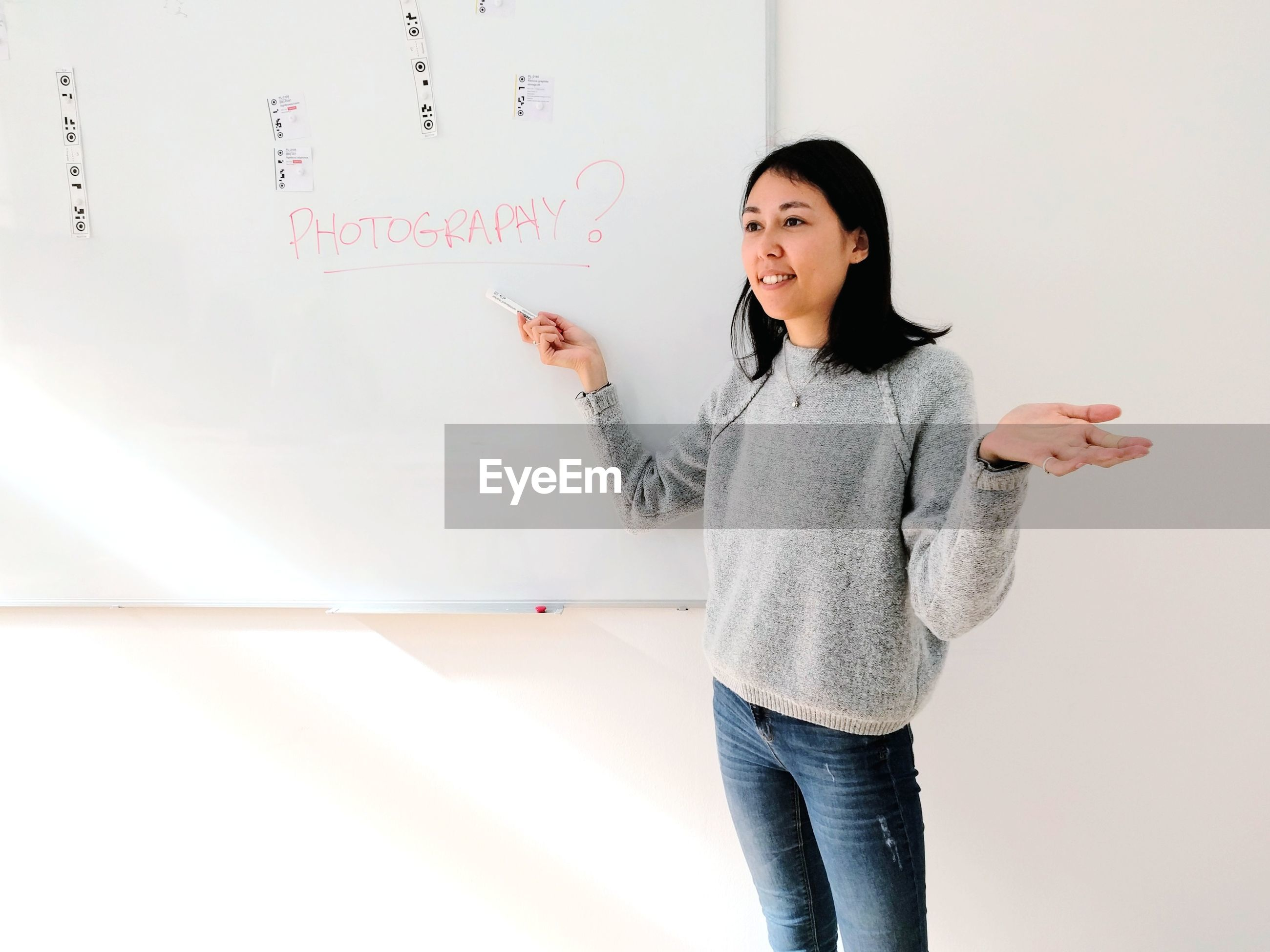 Young woman standing in front of whiteboard