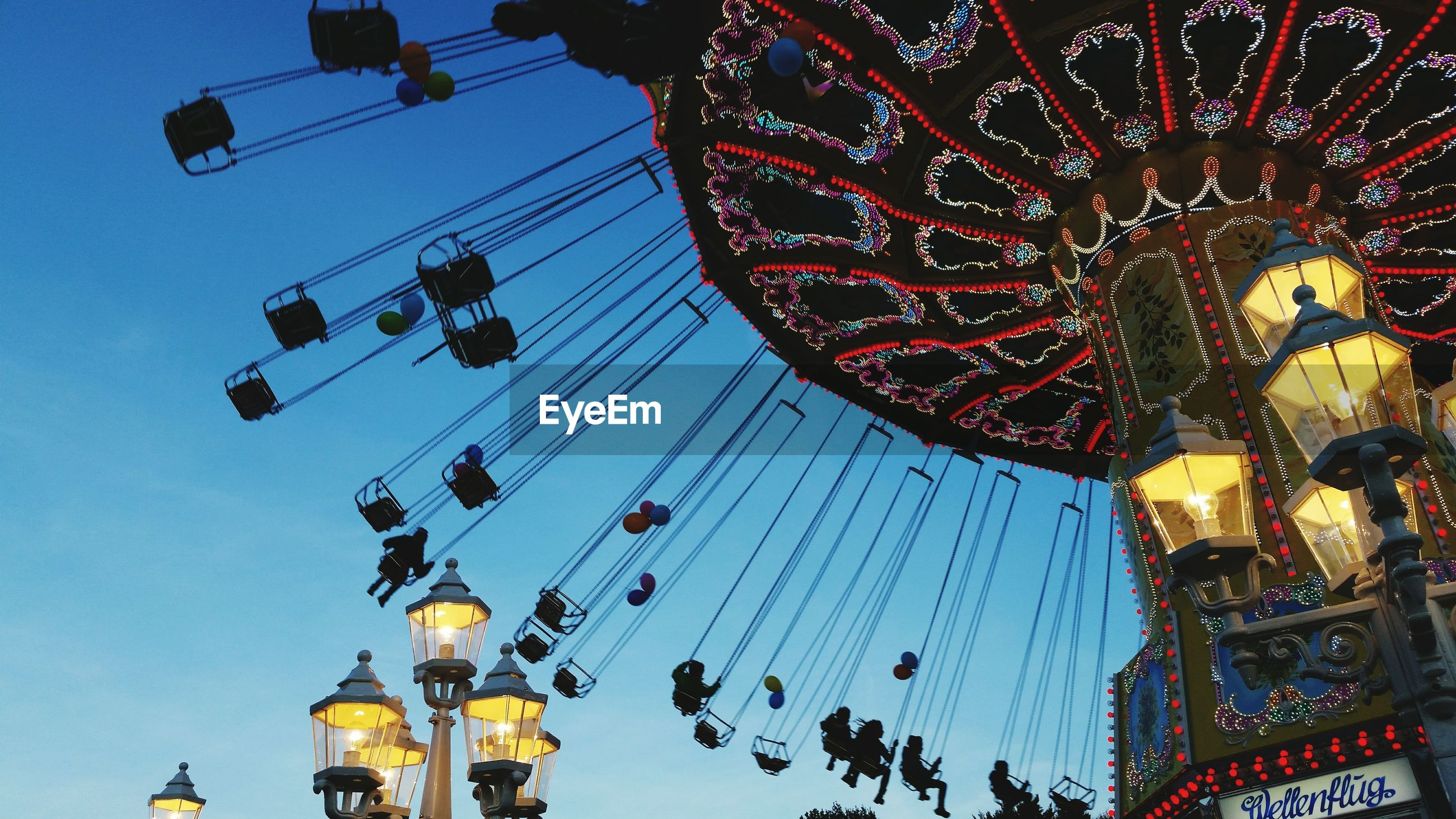 low angle view, amusement park, amusement park ride, arts culture and entertainment, illuminated, large group of people, ferris wheel, enjoyment, fun, celebration, leisure activity, sky, carousel, chain swing ride, lighting equipment, decoration, traveling carnival, cultures, night