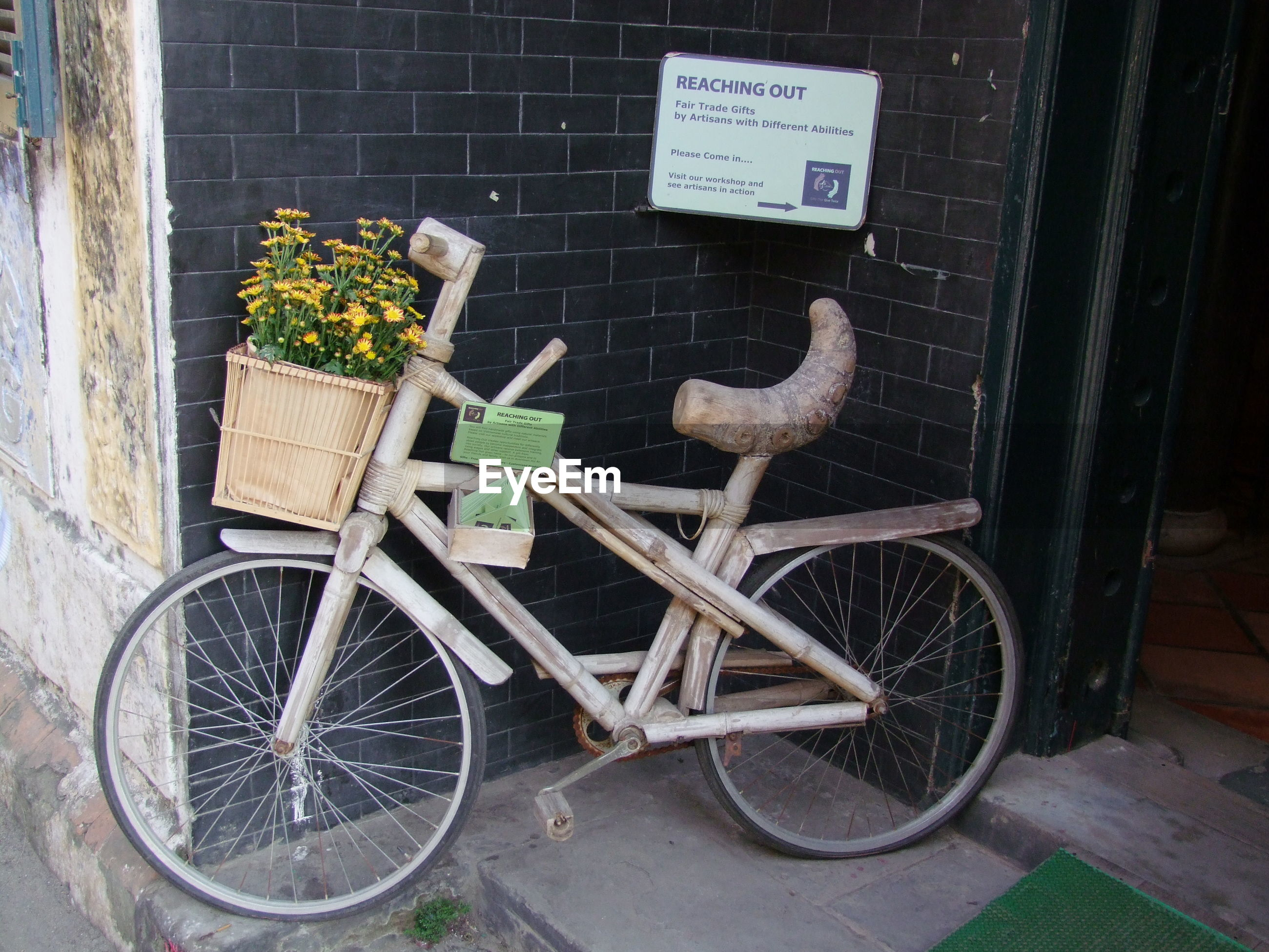 Wooden bicycle parked by wall