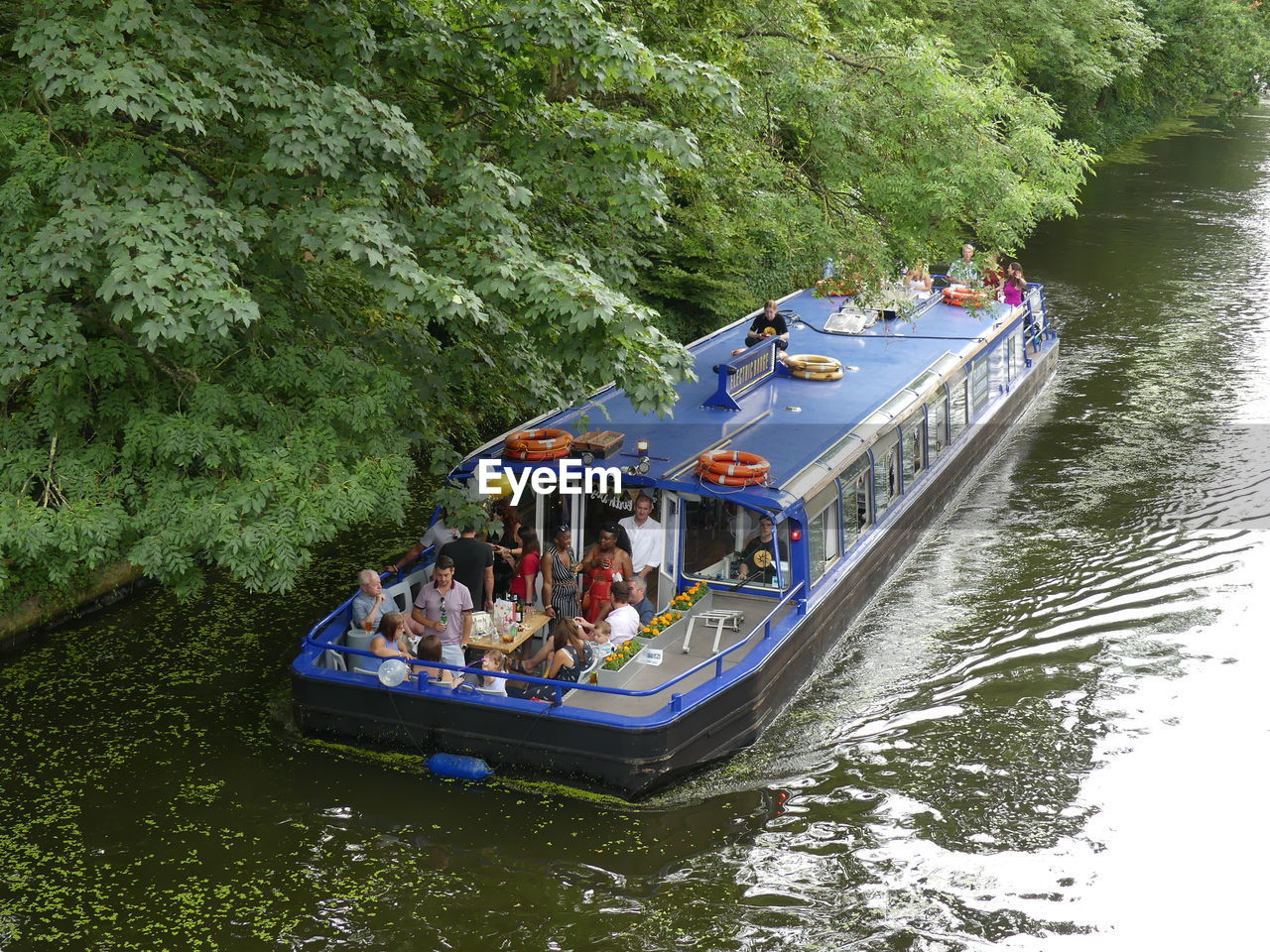 nautical vessel, water, transportation, group of people, tree, mode of transportation, plant, river, nature, day, crowd, large group of people, real people, waterfront, leisure activity, men, women, travel, outdoors, passenger craft, recreational boat