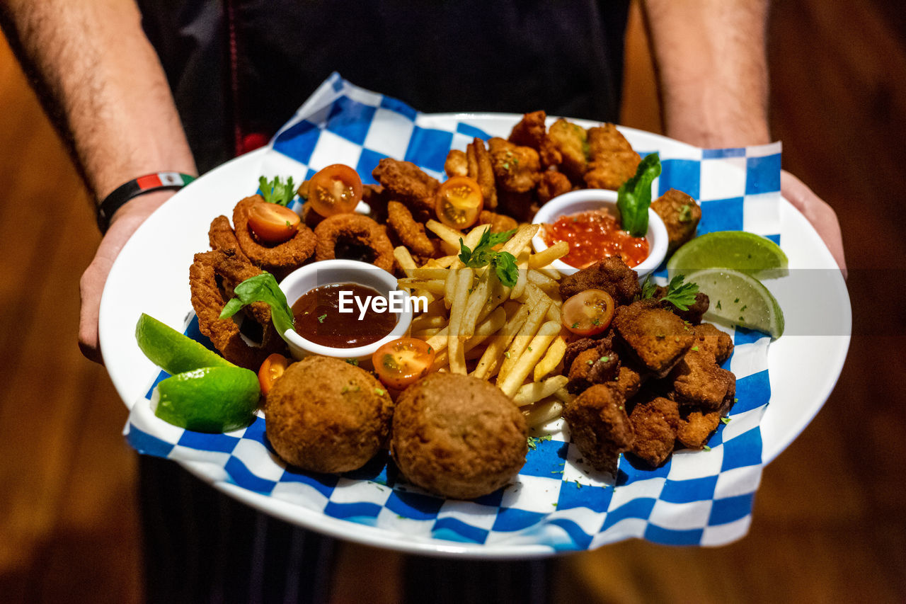 food, food and drink, ready-to-eat, plate, freshness, table, indoors, meat, serving size, focus on foreground, close-up, healthy eating, real people, wellbeing, bowl, midsection, lifestyles, one person, vegetable, high angle view, meal, snack