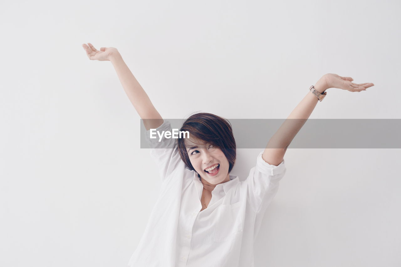 Cheerful young woman with arms raised against wall