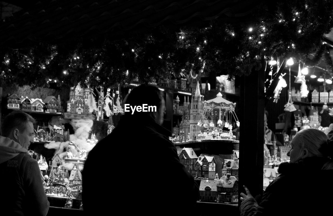 night, real people, retail, rear view, illuminated, women, small business, choice, store, food and drink, men, customer, consumerism, leisure activity, lifestyles, standing, indoors, nightlife, crowd, freshness, city, people