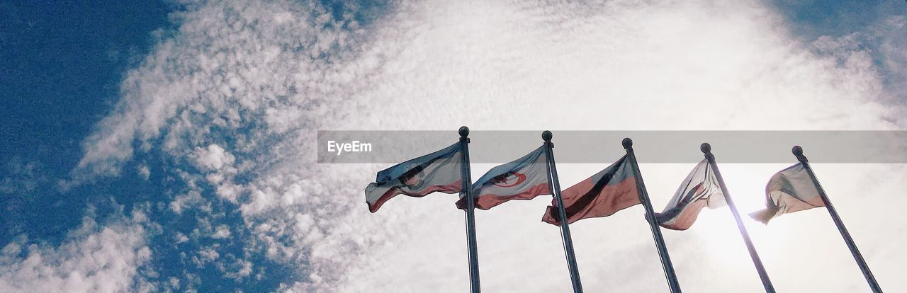 Panoramic of national flags against sky