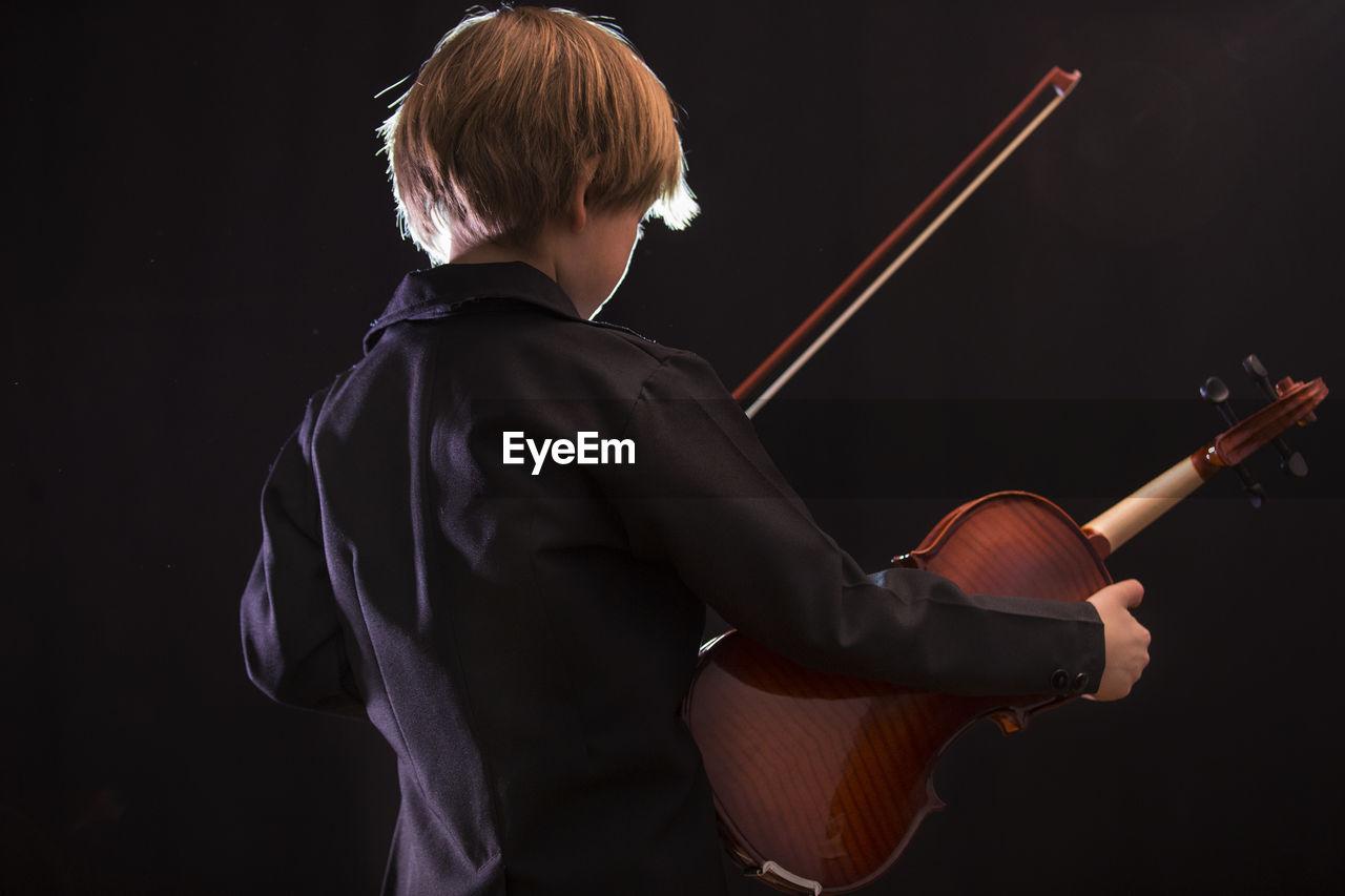Boy playing violin against black background
